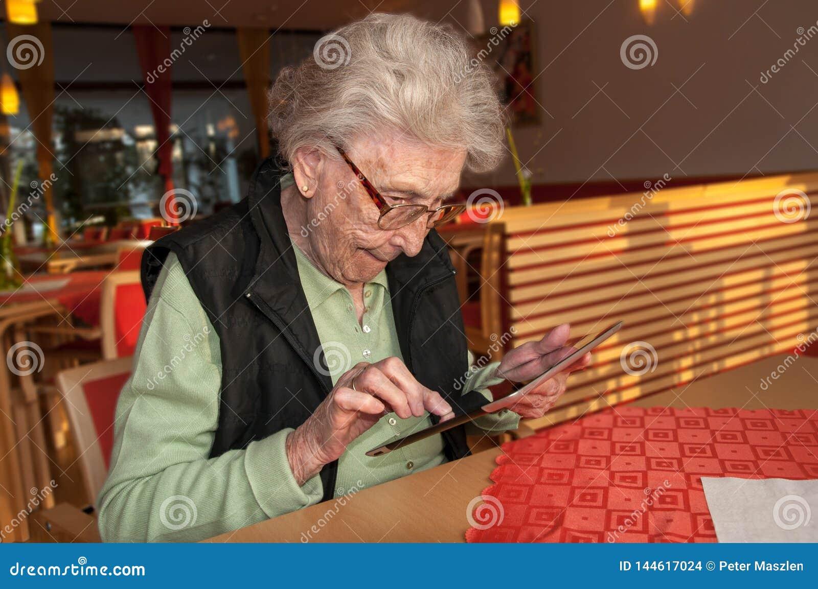 Ältere Frau, die Schirm des Tablet-Computers betrachtet