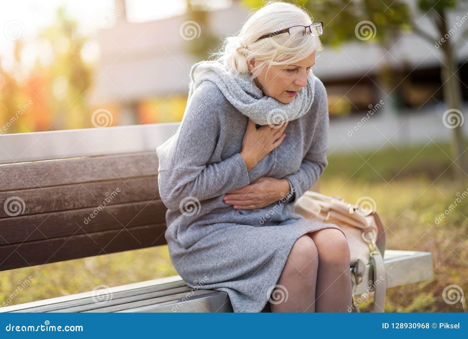 Ältere Frau, die unter Schmerz in der Brust leidet