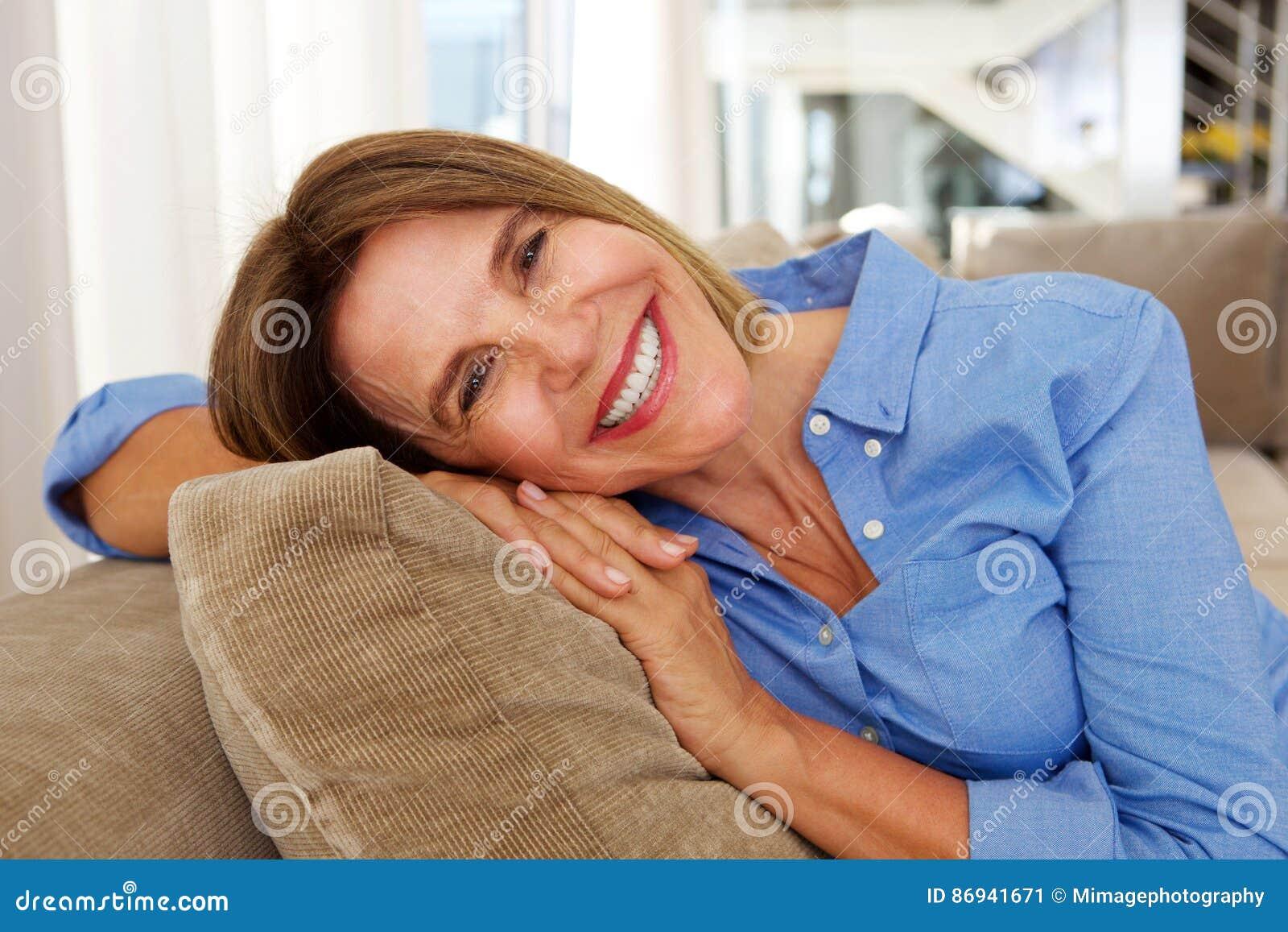 Ältere Frau, die zu Hause auf Sofa lächelt