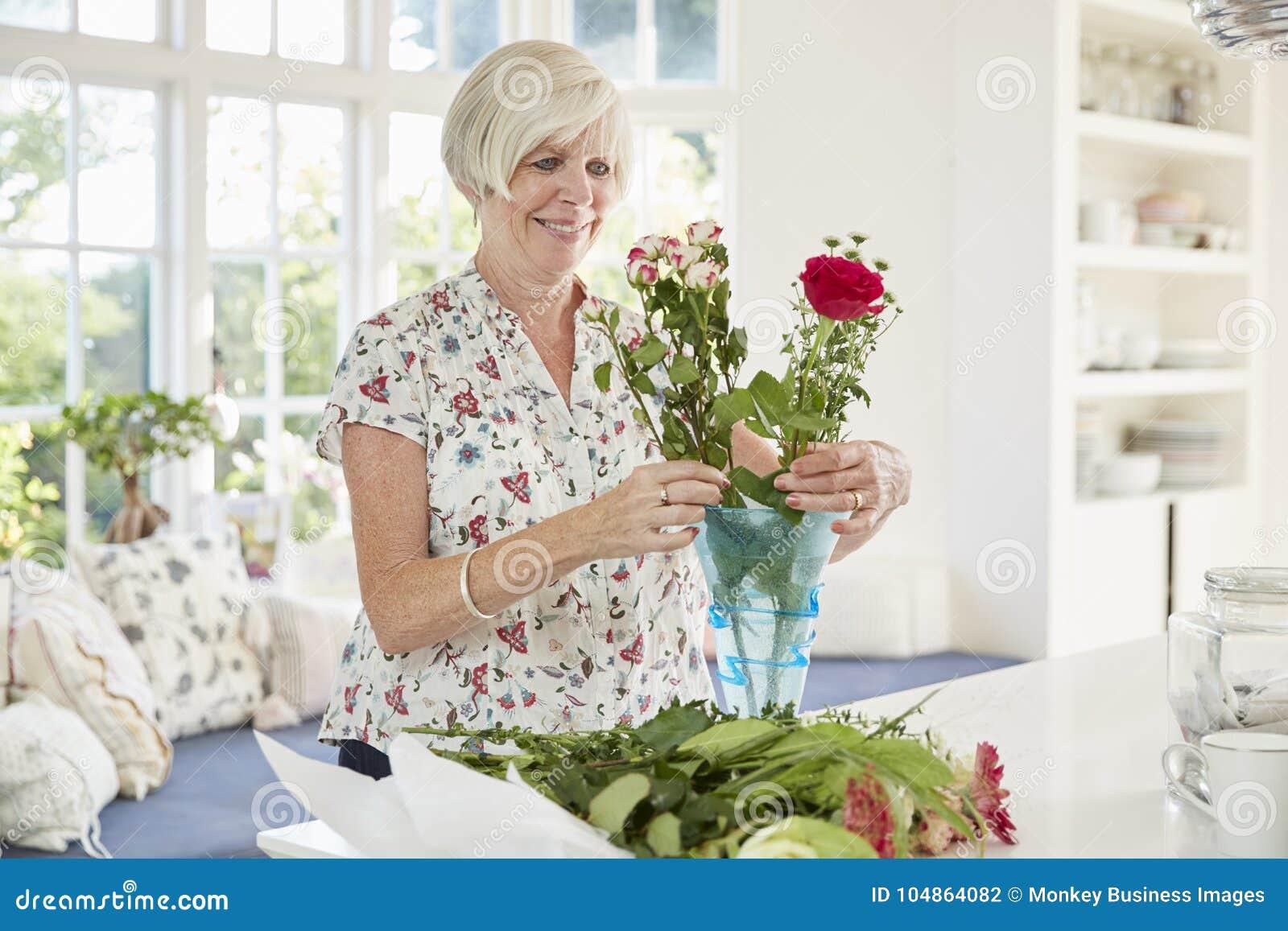 Ältere Frau, die zu Hause Blumen vereinbart