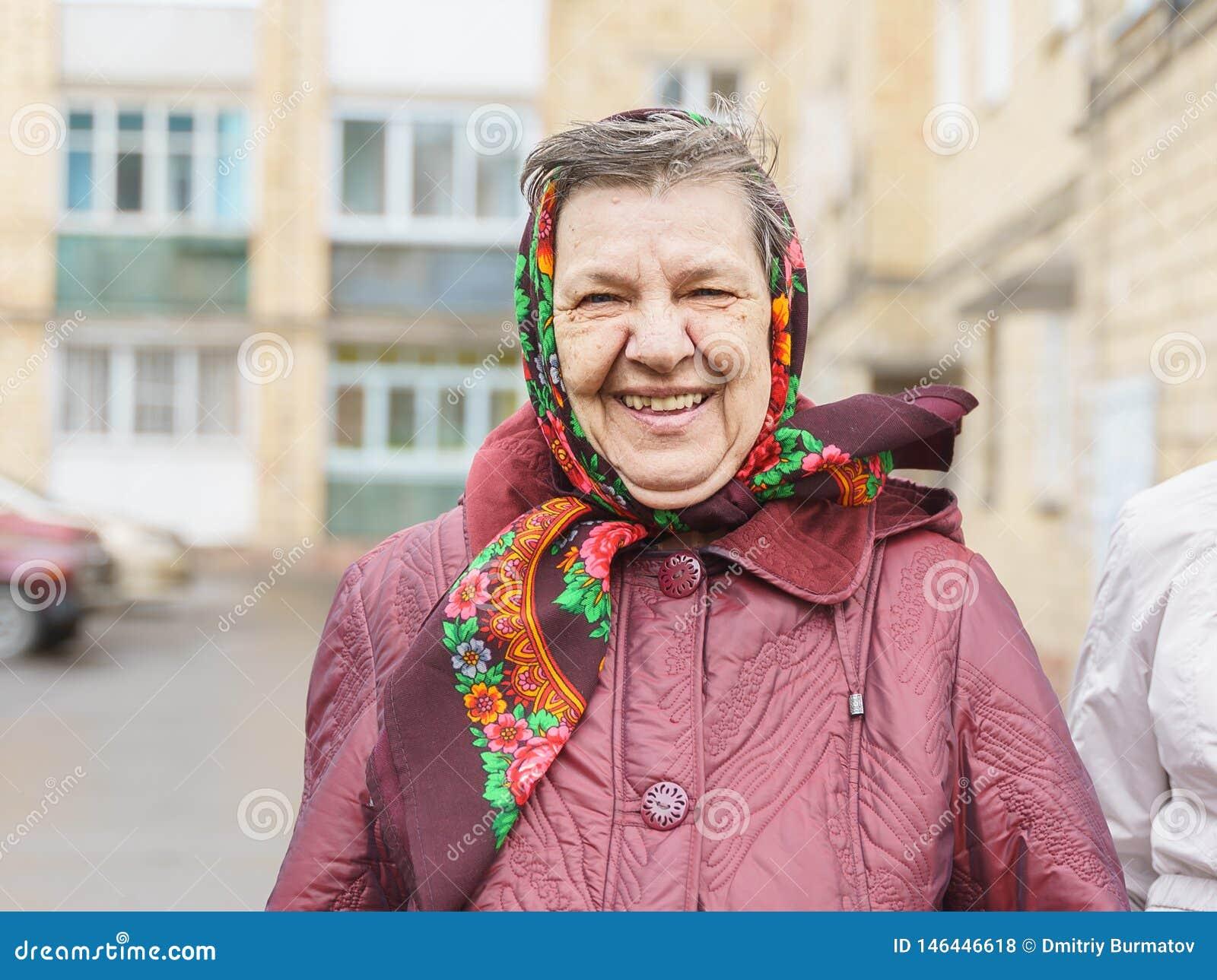 Ältere Frau in einem Kopftuch lächelt