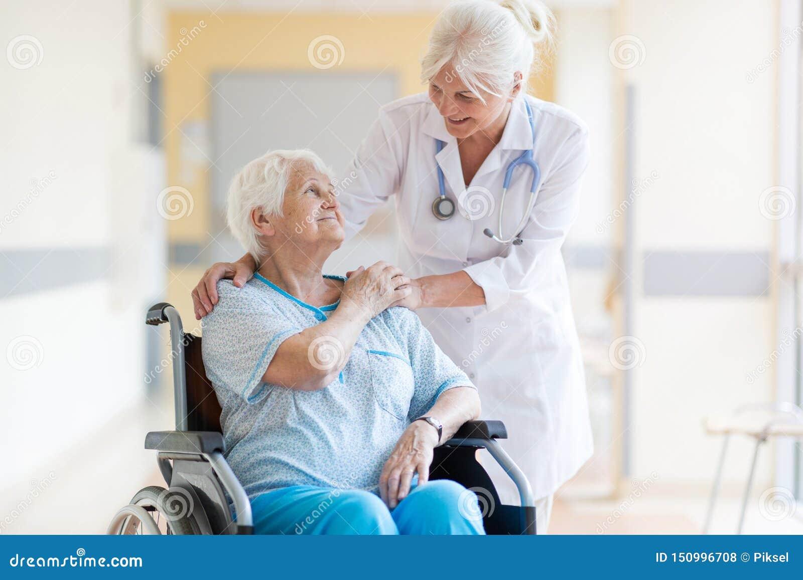 Ältere Frau im Rollstuhl mit Ärztin im Krankenhaus