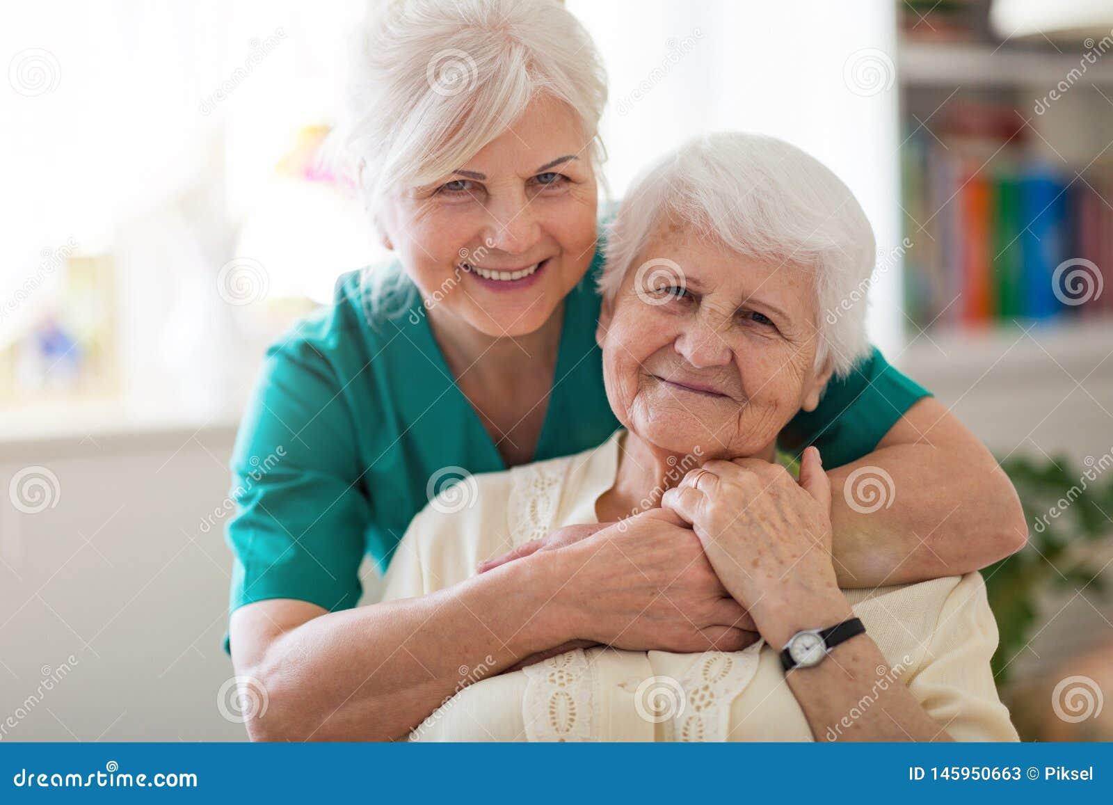 Ältere Frau mit ihrer weiblichen Pflegekraft