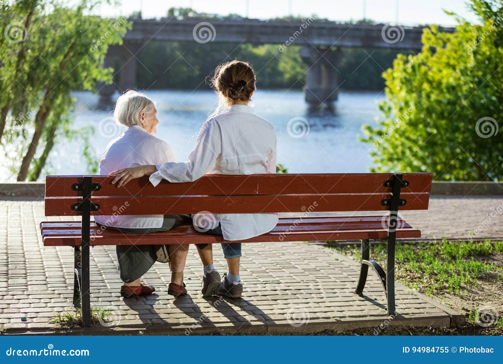 Ältere Frau und ihre erwachsene Enkelin, die auf Bank sitzt