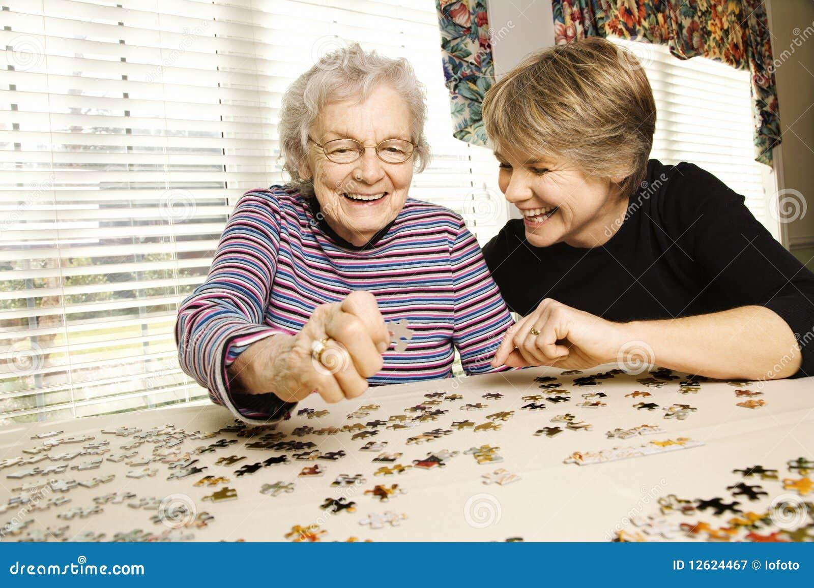Ältere Frau und jüngere Frau, die Puzzlespiel tut