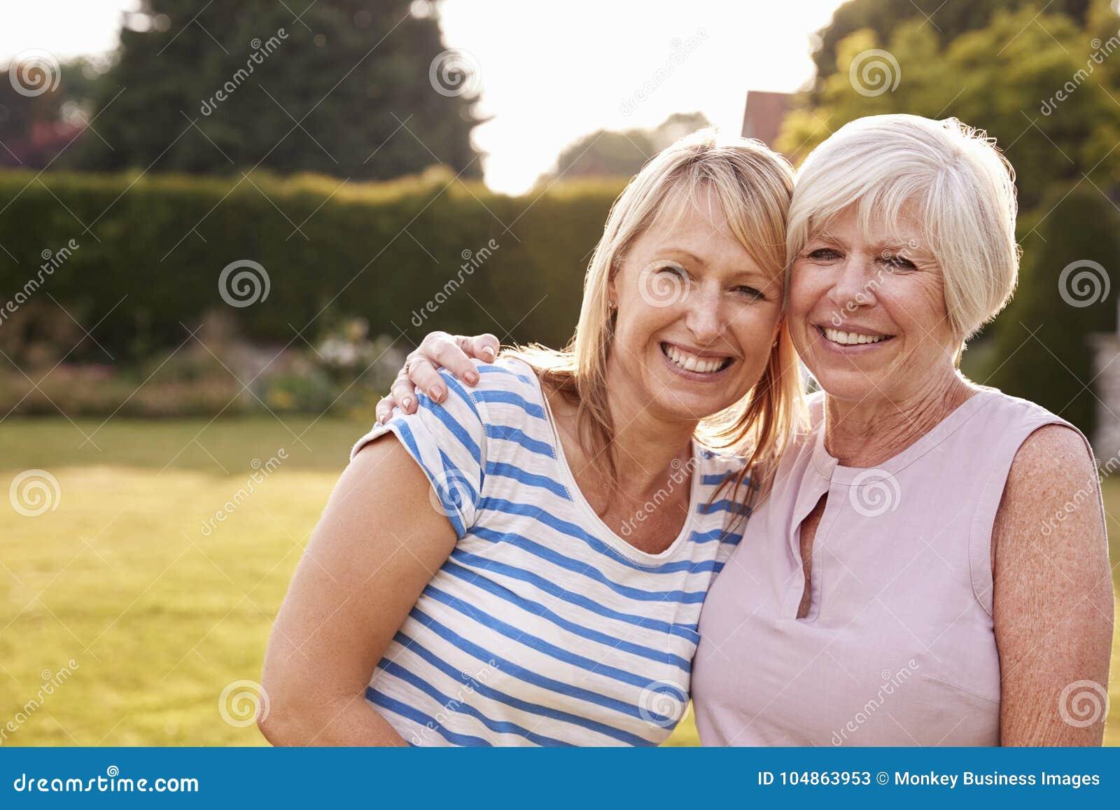Ältere Frauen- und Erwachsentochter, die im Garten umfasst