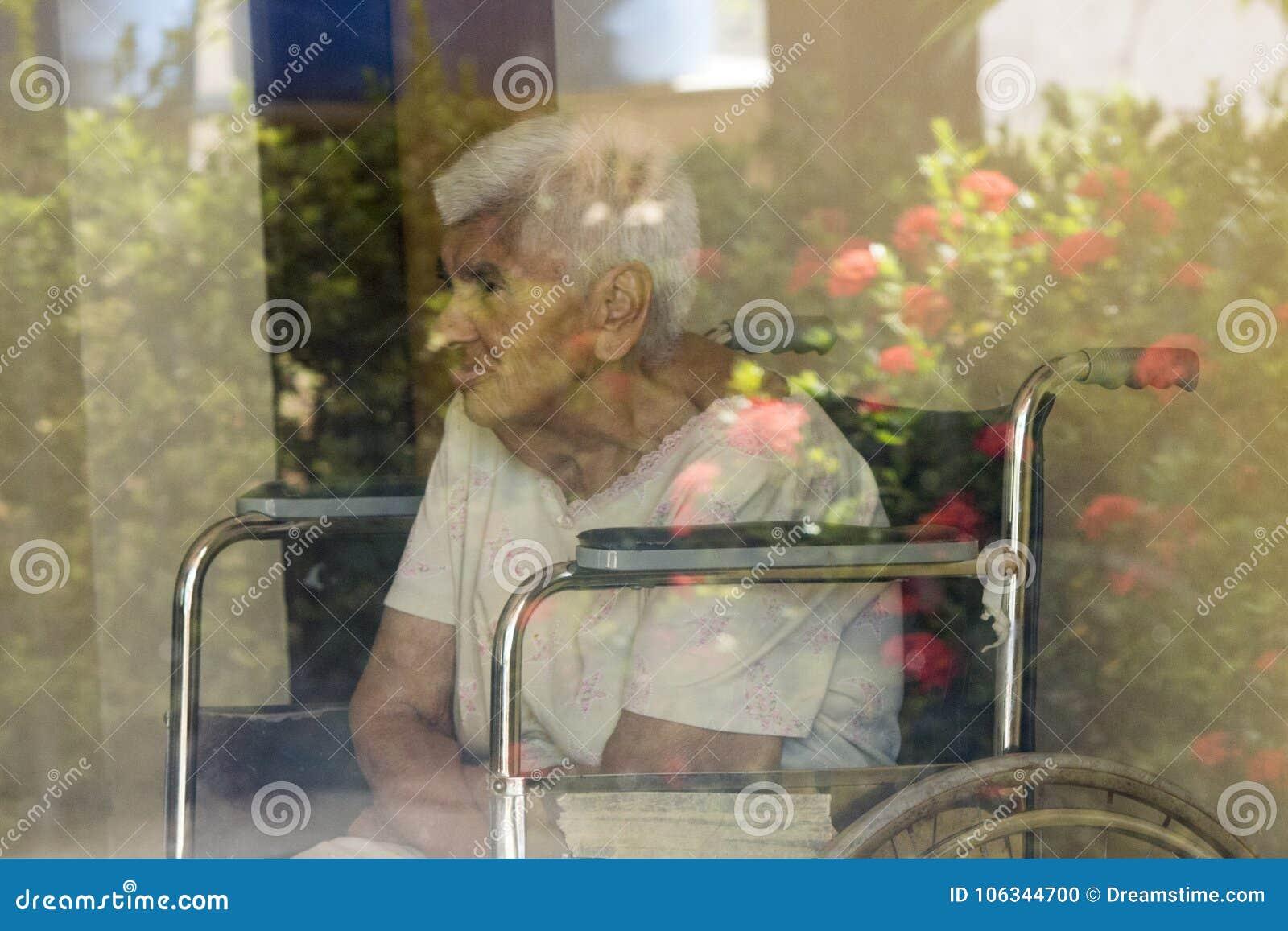 Ältere Frauenrollstuhlblumen