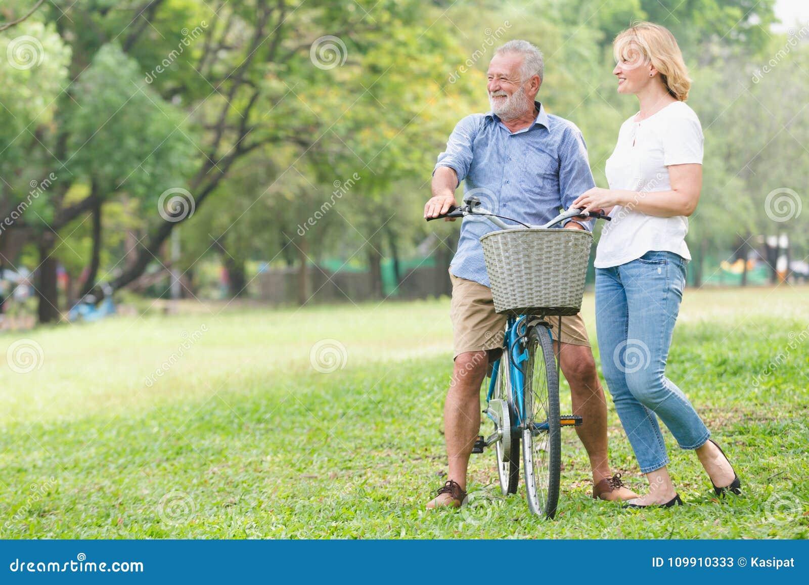 Ältere gehende Paare ihr Fahrrad