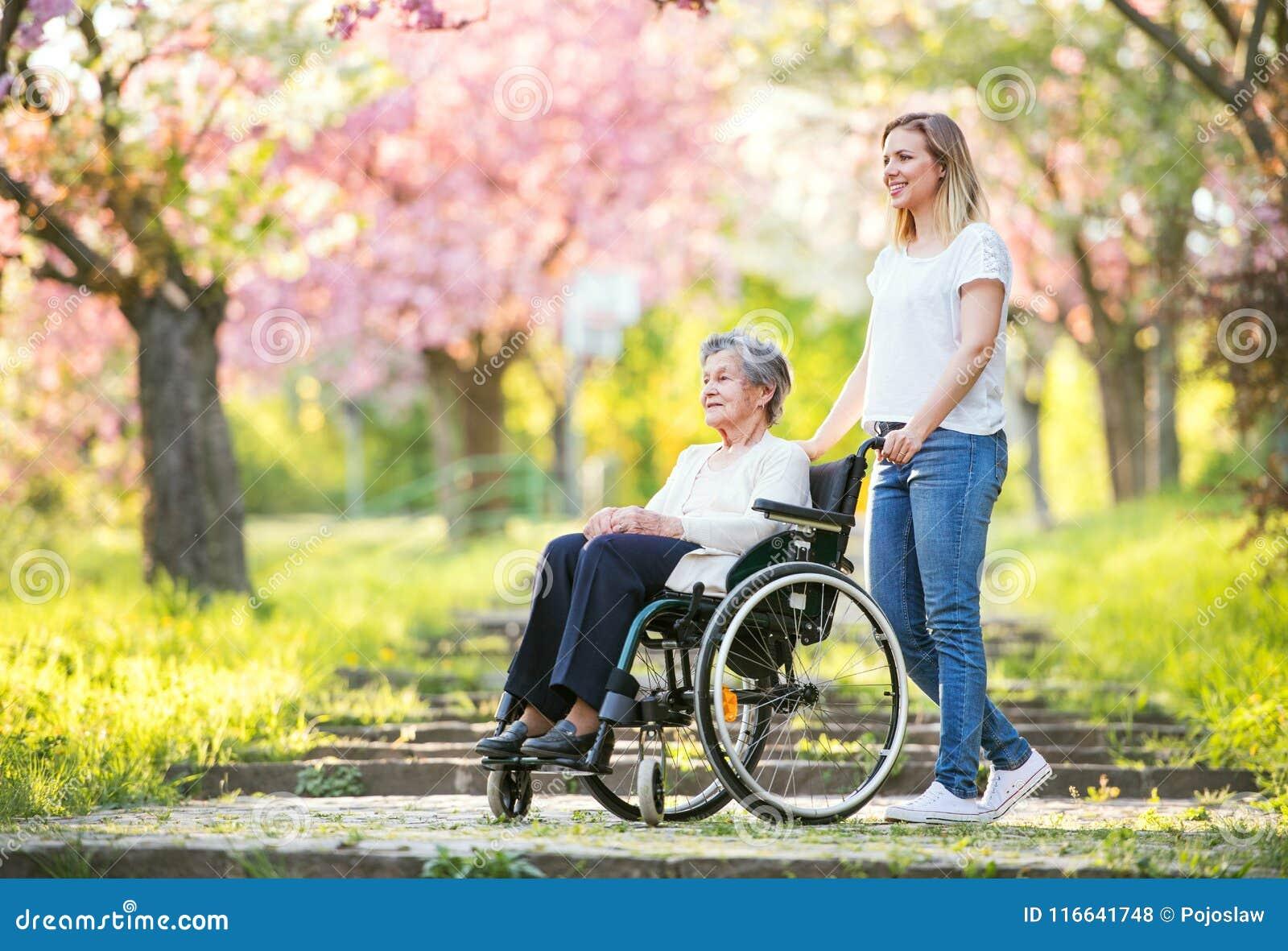 Ältere Großmutter im Rollstuhl mit Natur der Enkelin im Frühjahr