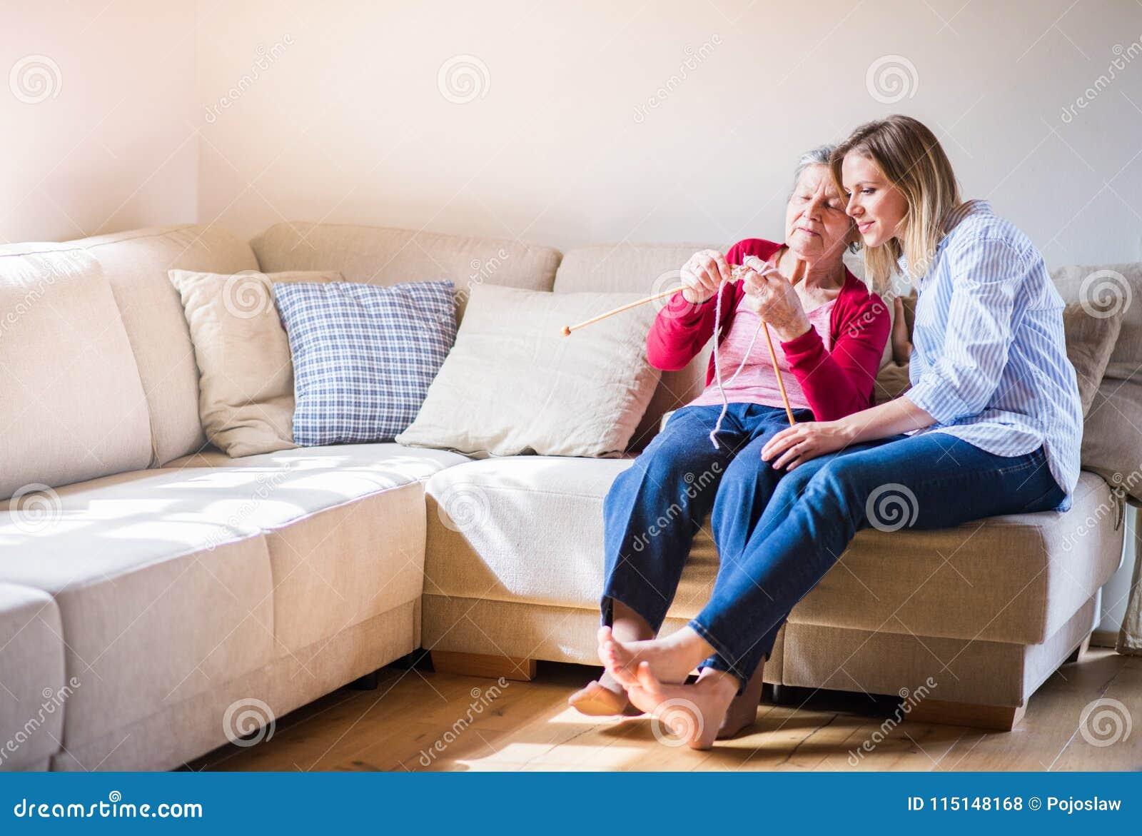 Ältere Großmutter- und Erwachsenenkelin zu Hause, strickend