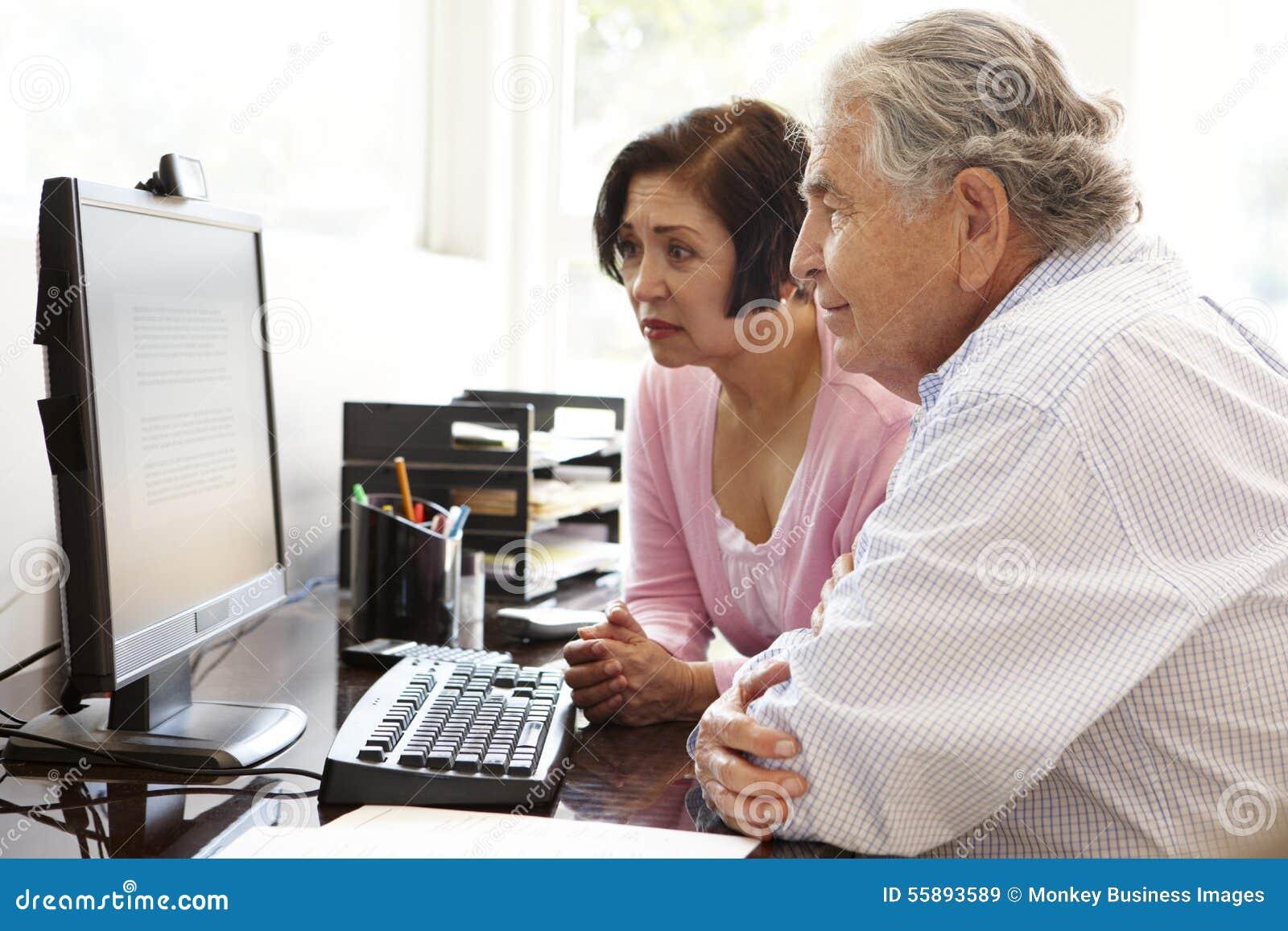 Ältere hispanische Paare, die zu Hause an Computer arbeiten