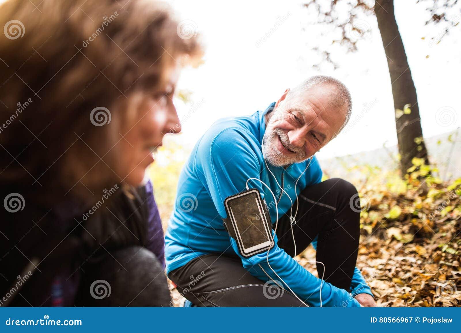 Ältere Läufer in der Natur, Spitzee binden Mann mit smartphone