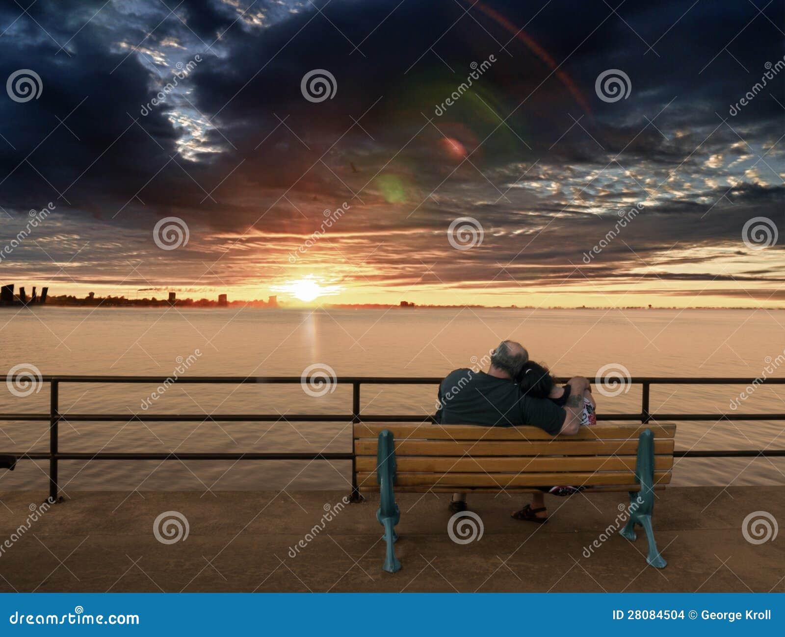 Ältere Paare auf der Bank, die Sonnenuntergang genießt