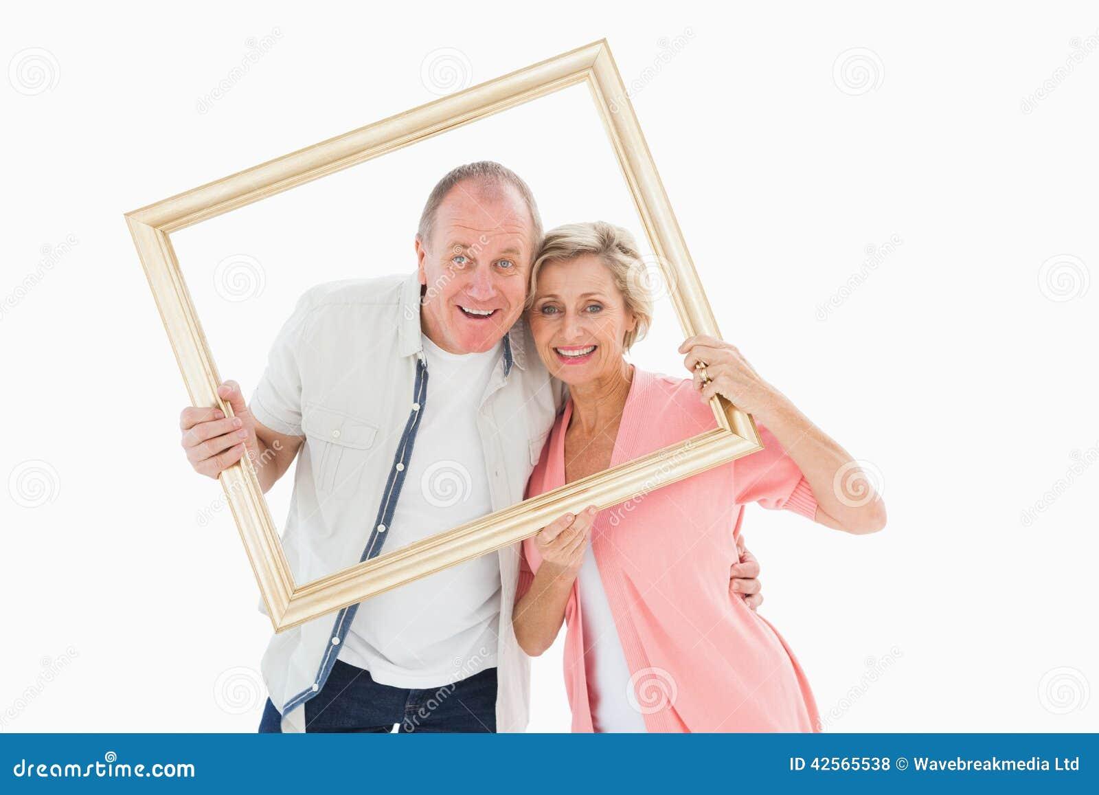 Ältere Paare, Die An Der Kamera Durch Bilderrahmen Lächeln Stockfoto ...