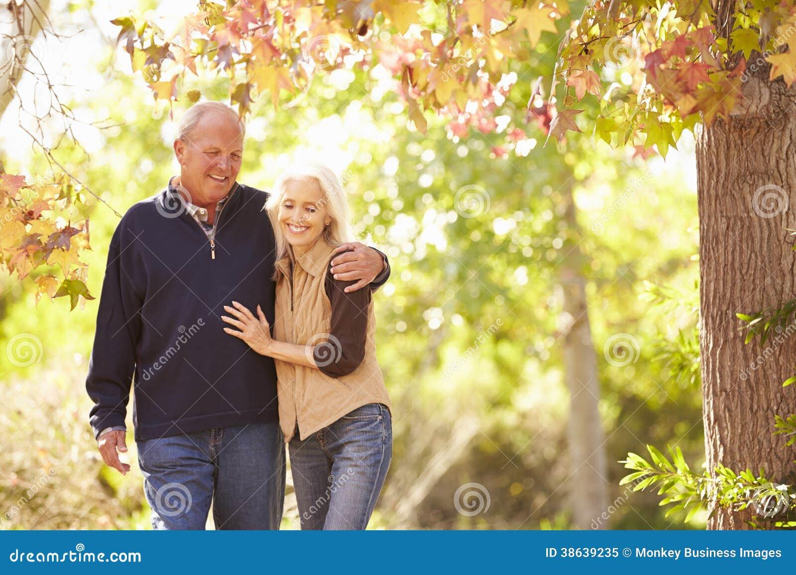 Ältere Paare, die durch Autumn Woodland gehen