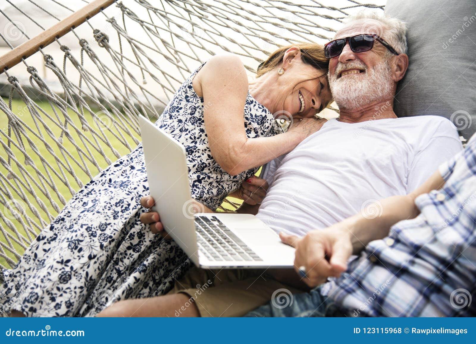 Ältere Paare, die in einer Hängematte sich entspannen