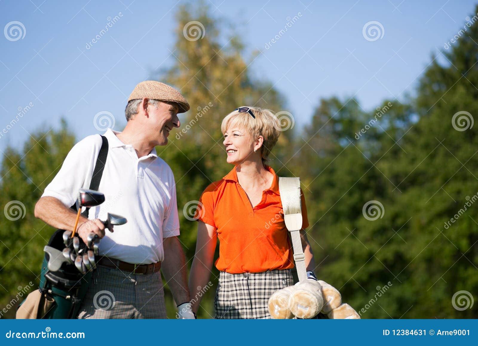 Ältere Paare, die Golf spielen