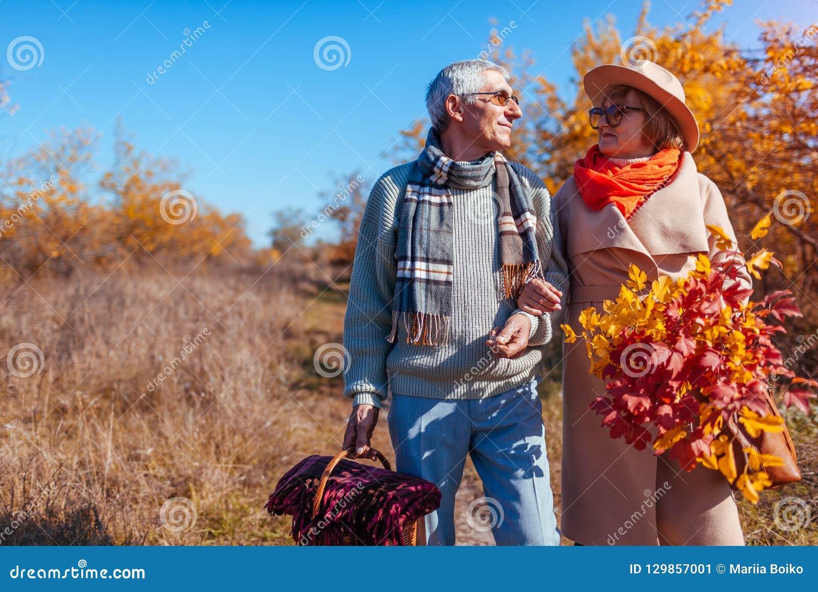 Ältere Paare, die in die Herbstwaldmann von mittlerem Alter und -frau draußen umarmt und kühlt gehen