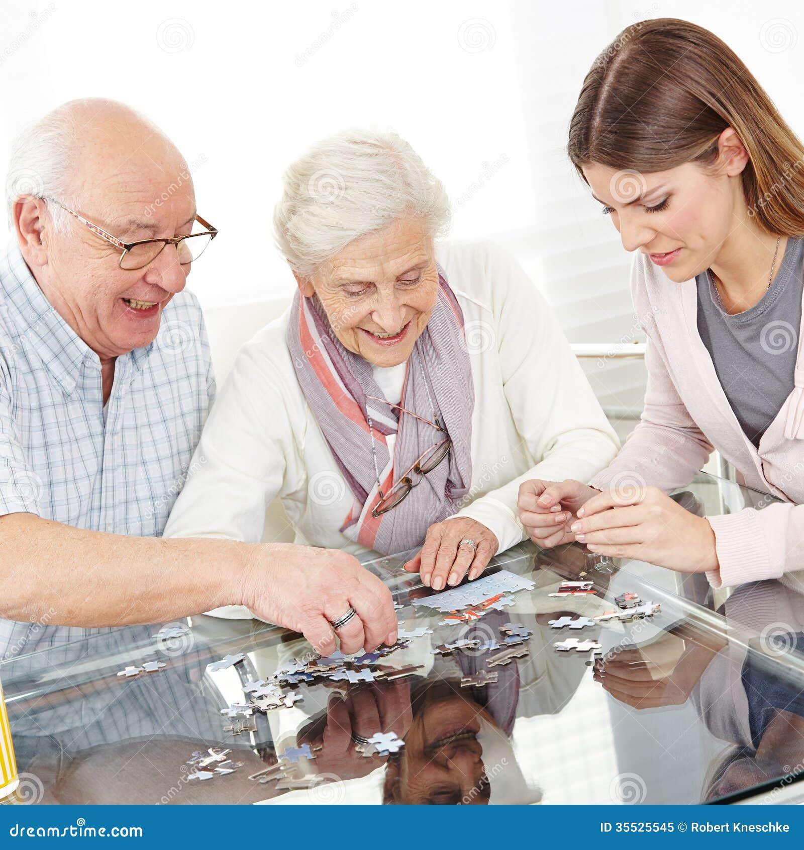 Ältere Paare, die Puzzlen lösen
