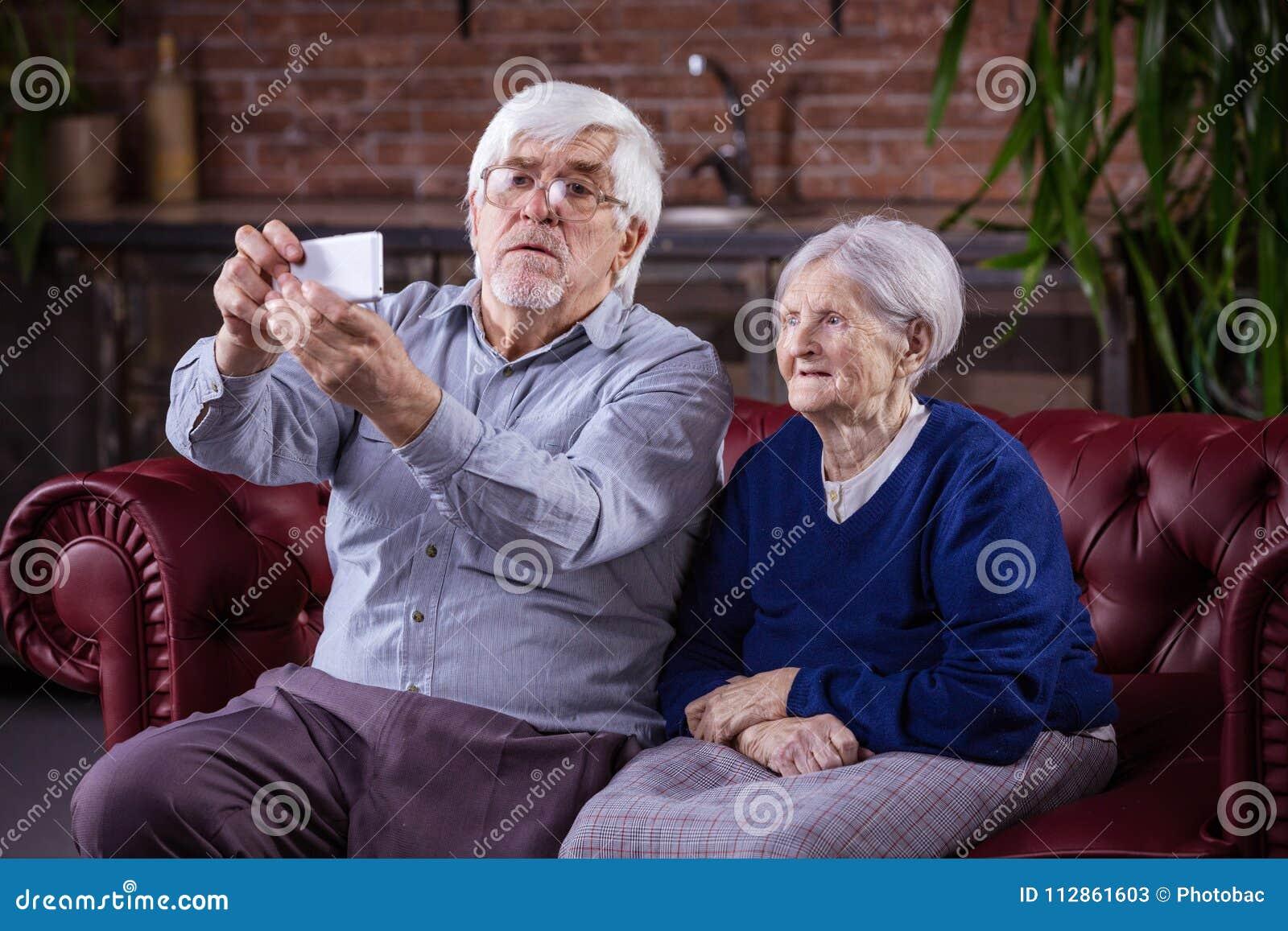Ältere Paare, die selfie am intelligenten Telefon beim Sitzen auf couc nehmen