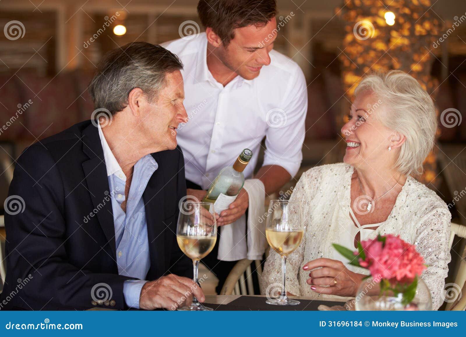 Ältere Paare Kellner-Serving Wine Tos im Restaurant