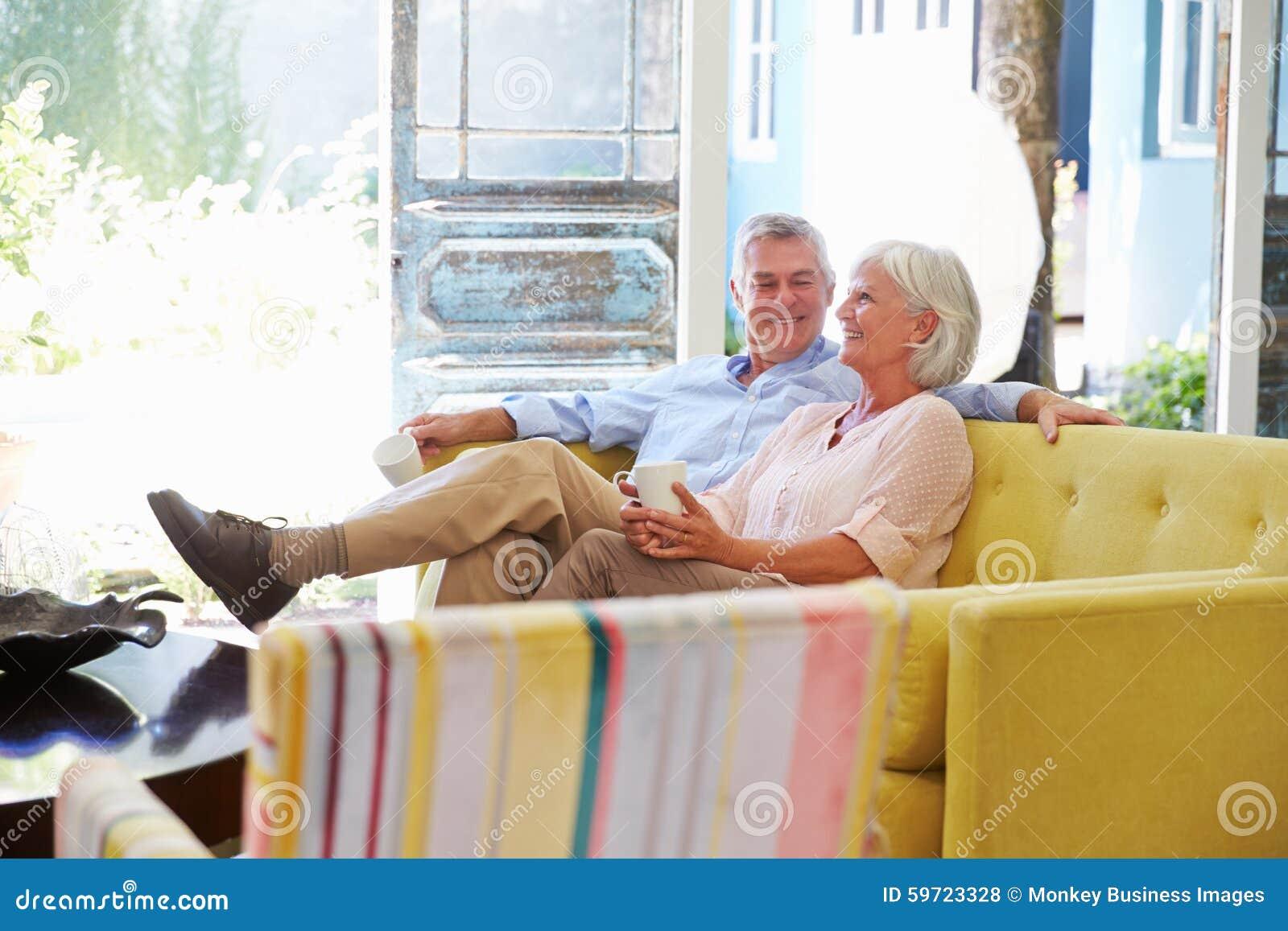 Ältere Paare zu Hause, die im Aufenthaltsraum mit heißem Getränk sich entspannen