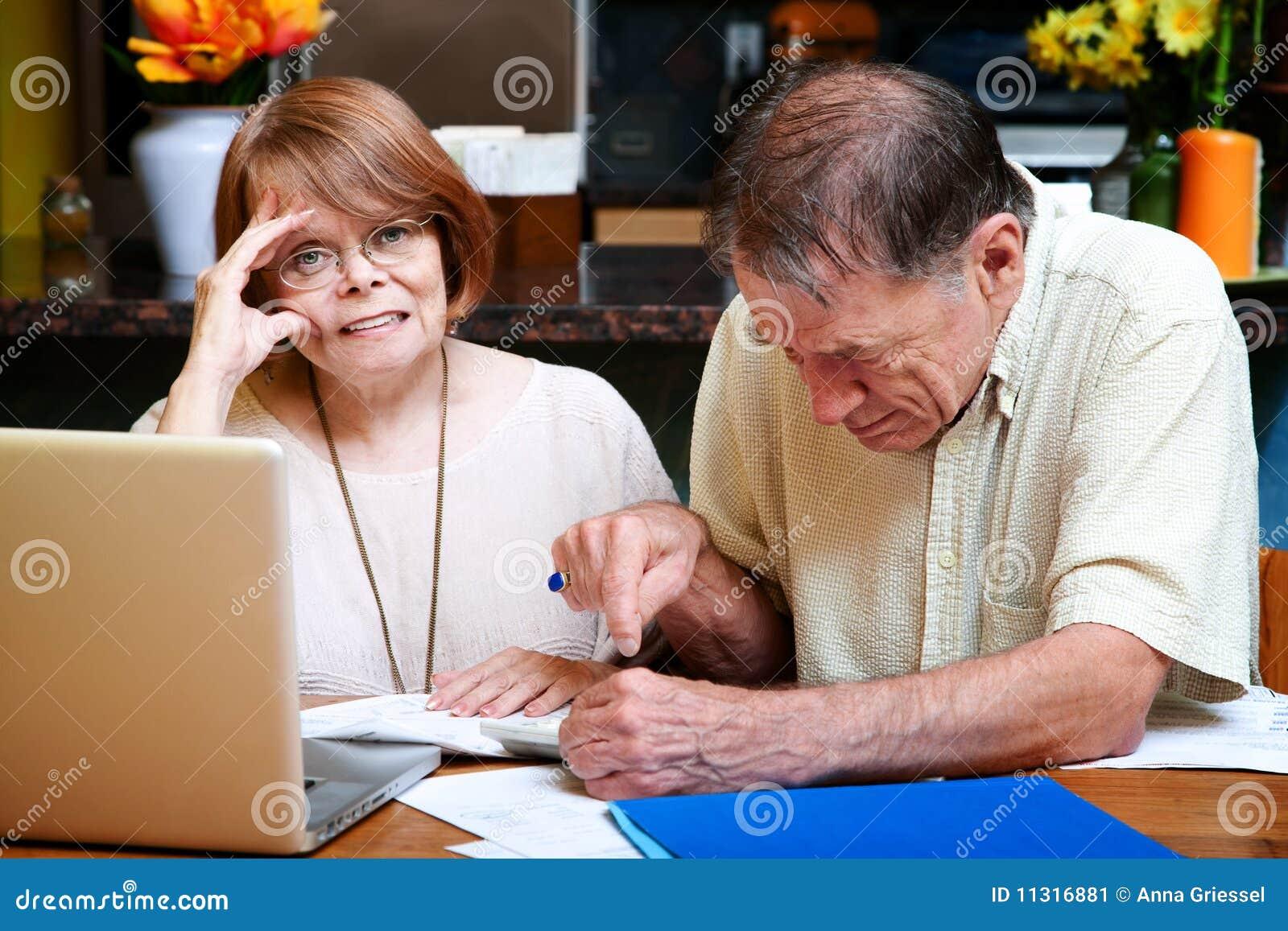 Ältere Paare zu Hause mit vielen Rechnungen