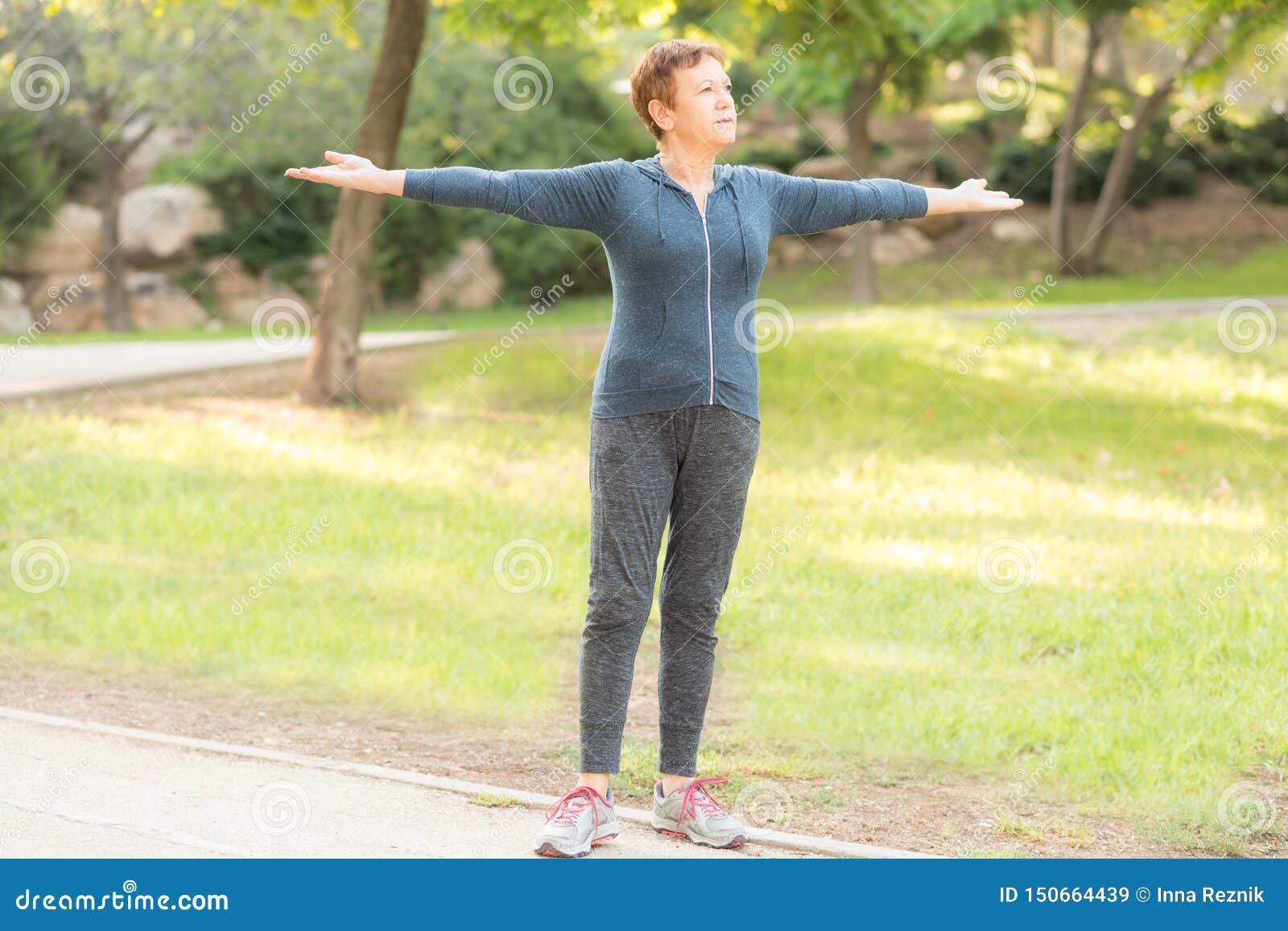 Ältere schöne aktive glückliche Frau morgens im Herbstpark, der Sportübungen tut