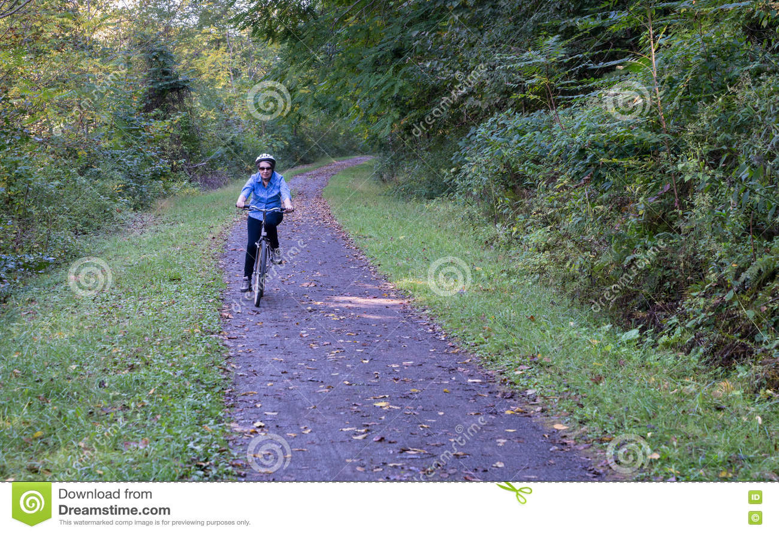 Ältere Zyklen der erwachsenen Frau in Richtung zur Kamera