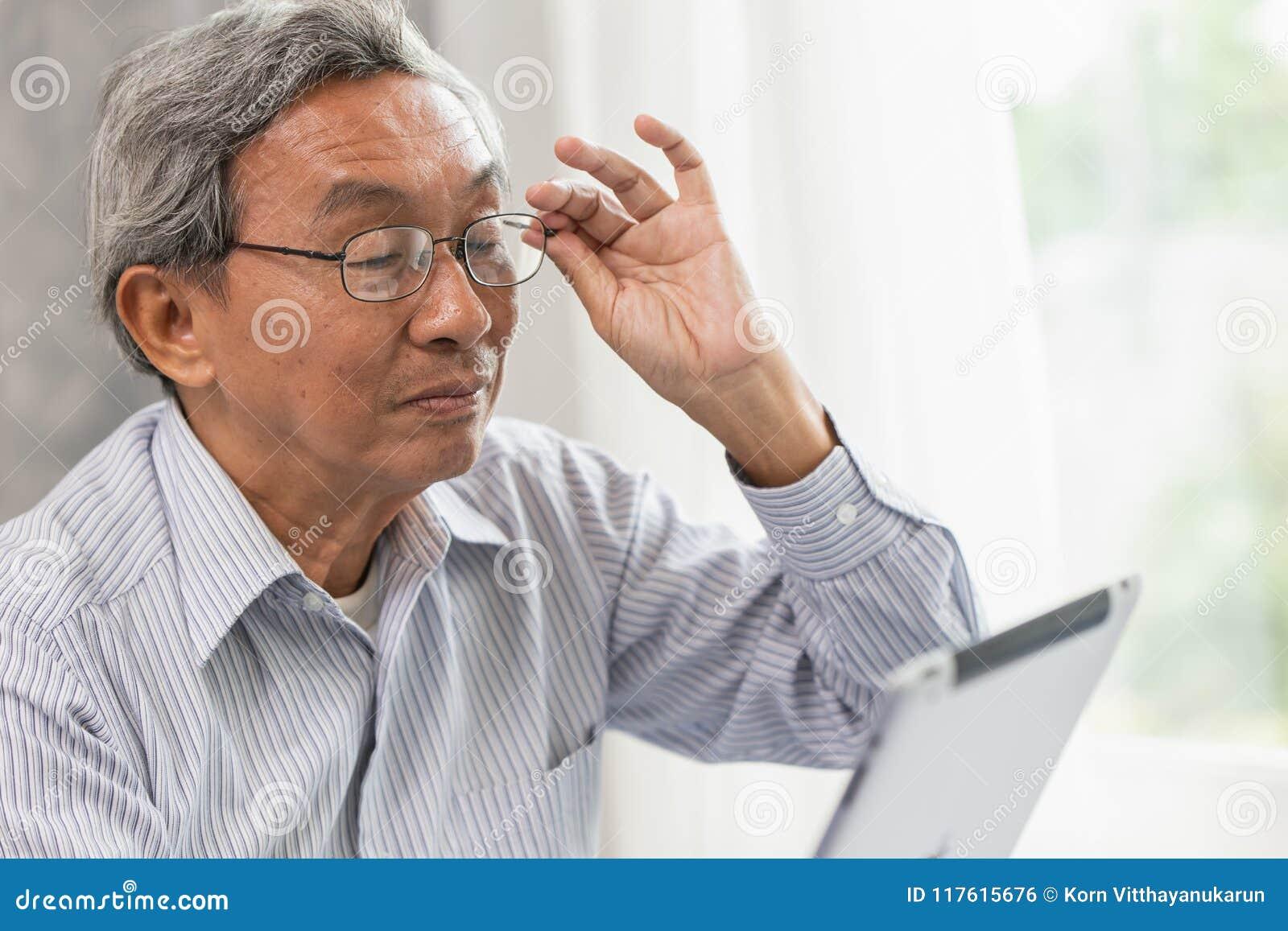 älterer alter Mann der Gläser glücklich unter Verwendung des Betrachtens des Tabletschirmes