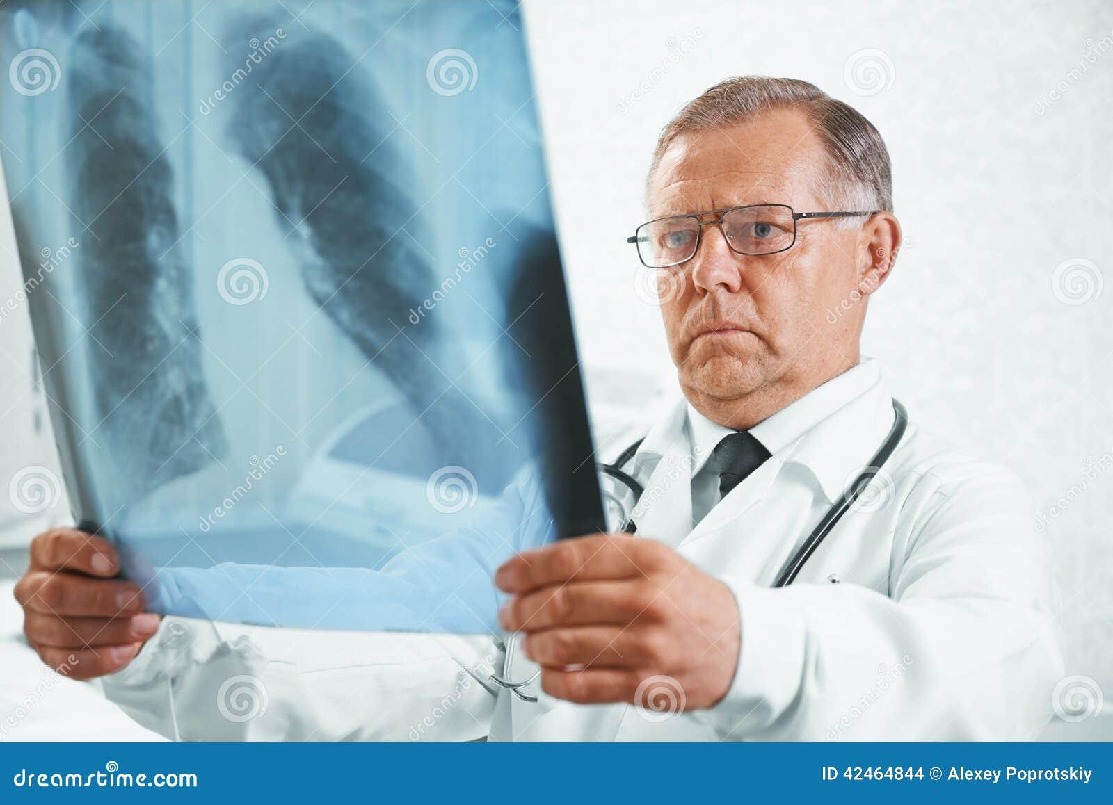 Älterer Doktor überprüft Röntgenstrahlbild von Lungen