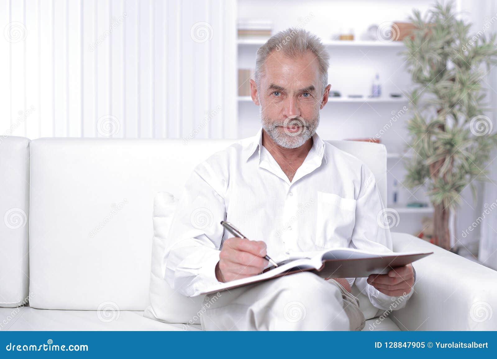 Älterer Geschäftsmann, der eine Anmerkung im Arbeitsbuch macht