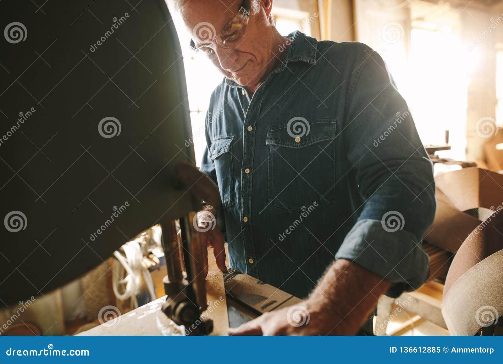 Älterer männlicher Tischler, der an Bandsägemaschine arbeitet