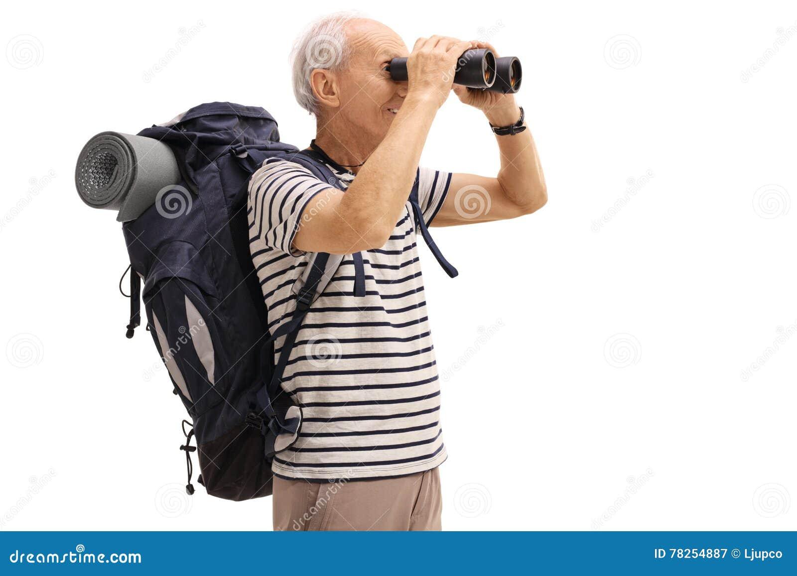 Älterer männlicher wanderer der durch ferngläser schaut stockbild