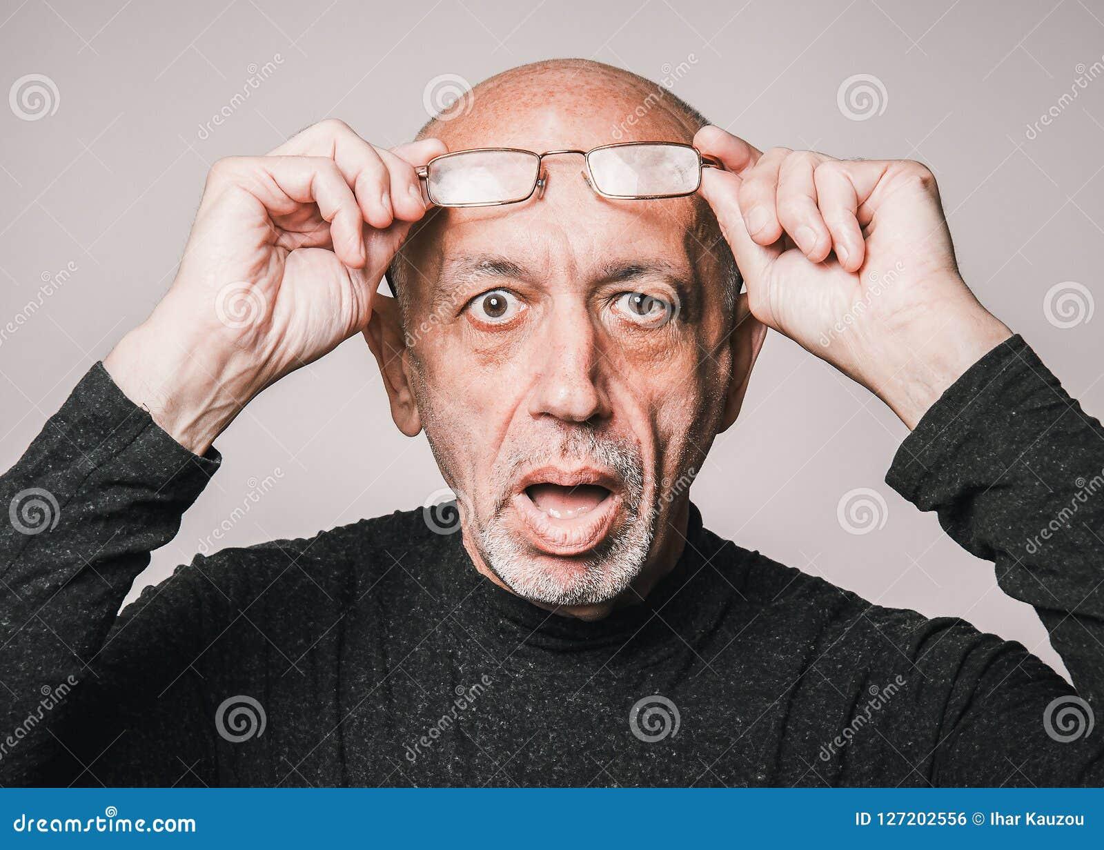 Älterer, älterer Mann in den Gläsern, schauend entsetzt