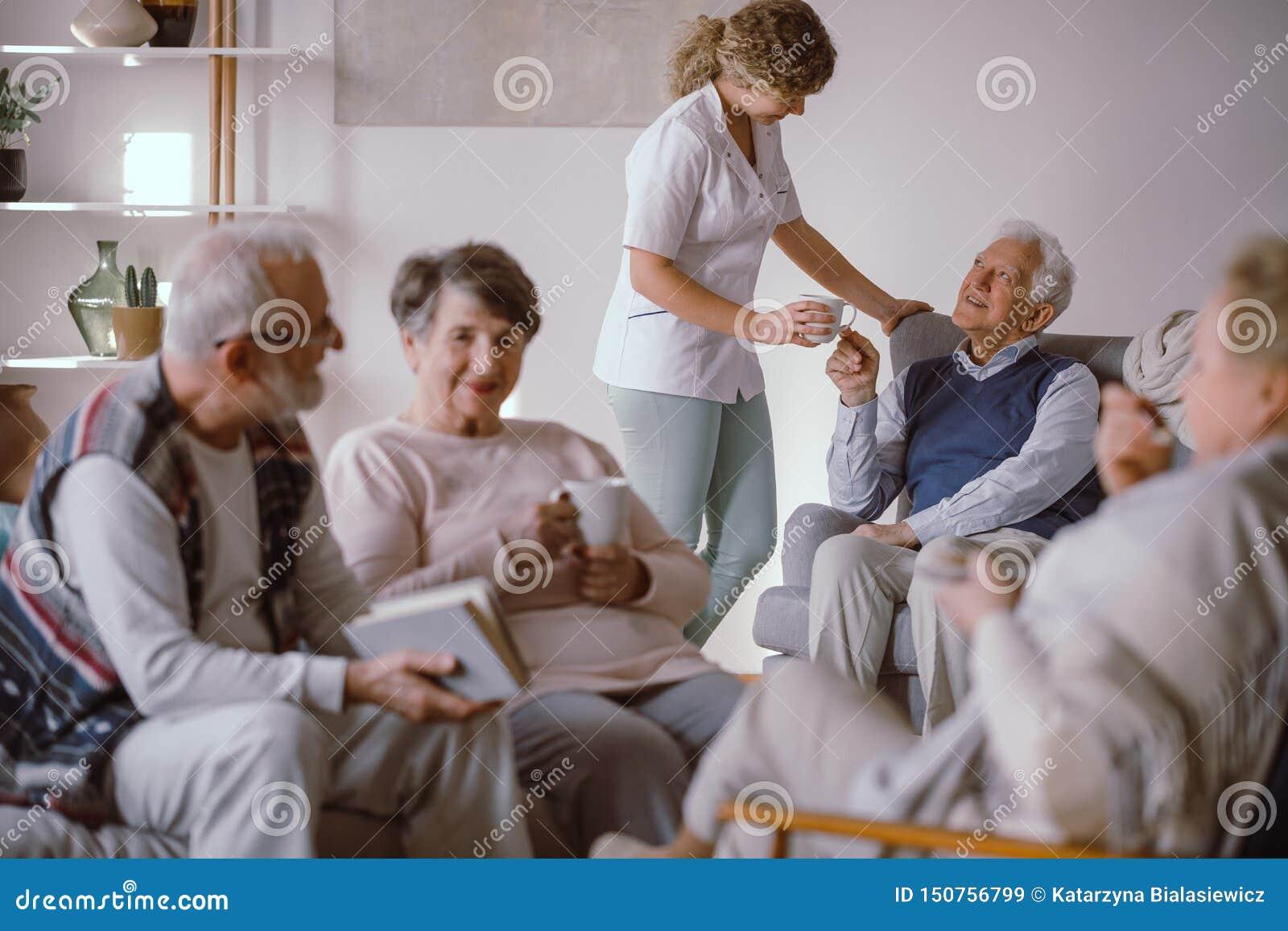 Älterer Mann, der eine Tasse Tee von seiner Pflegekraft im Pflegeheim nimmt