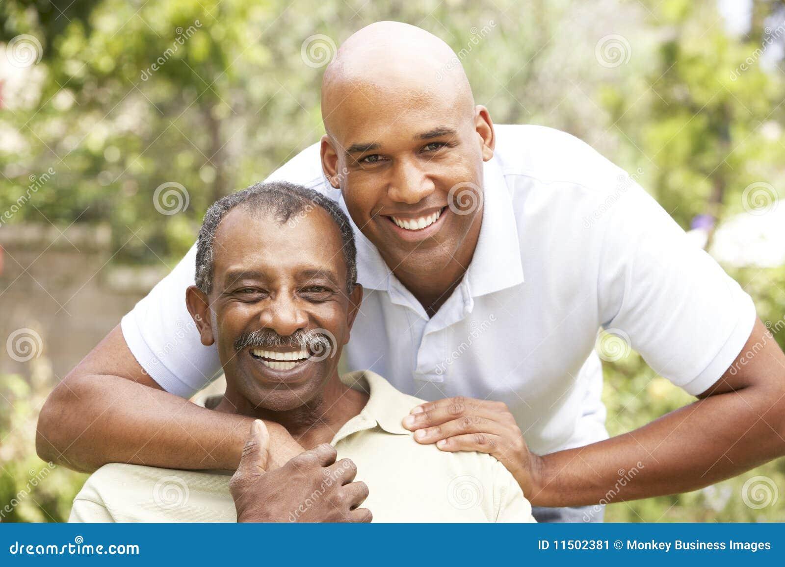 Älterer Mann, der erwachsenen Sohn umarmt