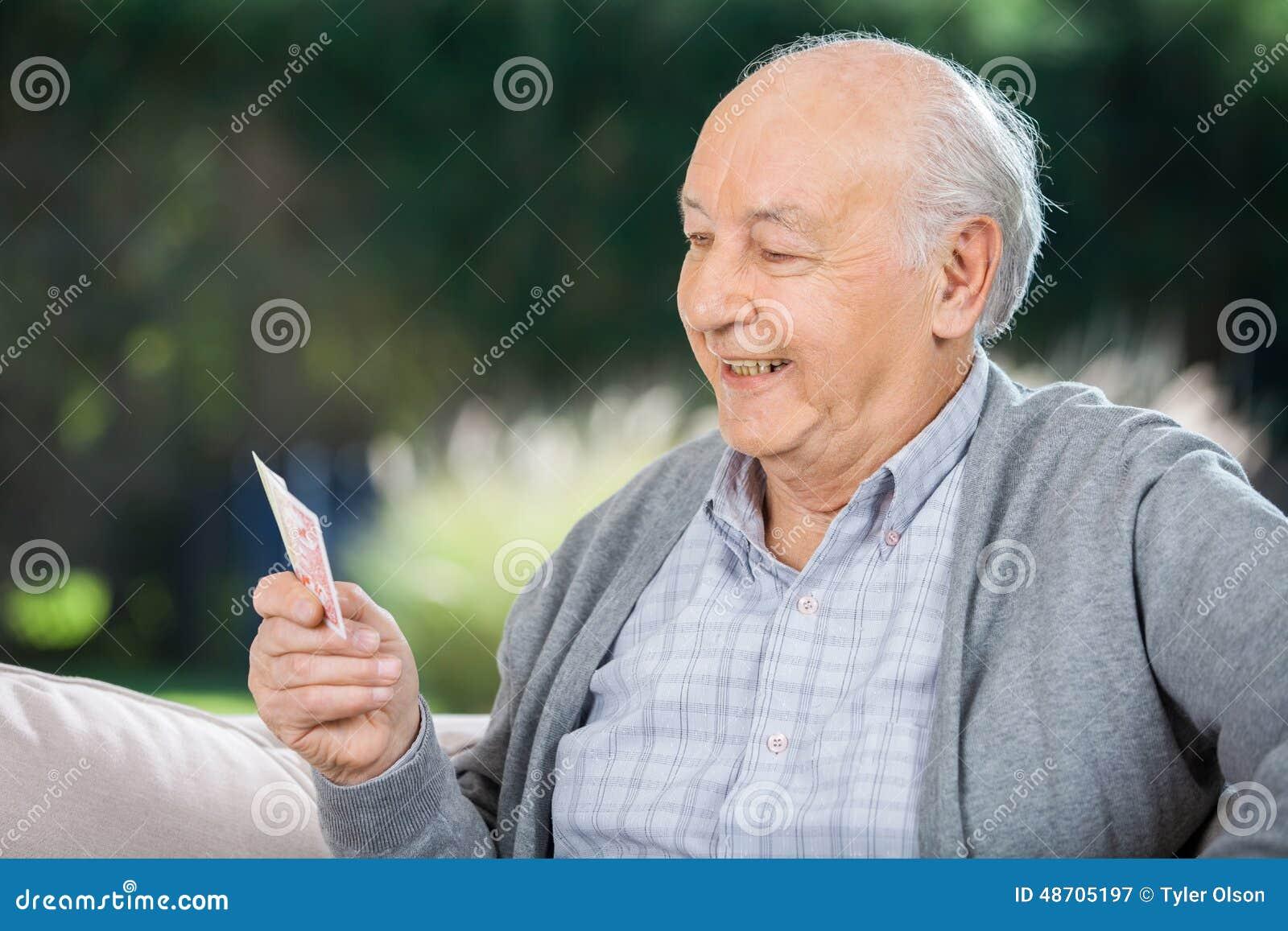 Älterer Mann, der Karten beim Sitzen auf Couch betrachtet