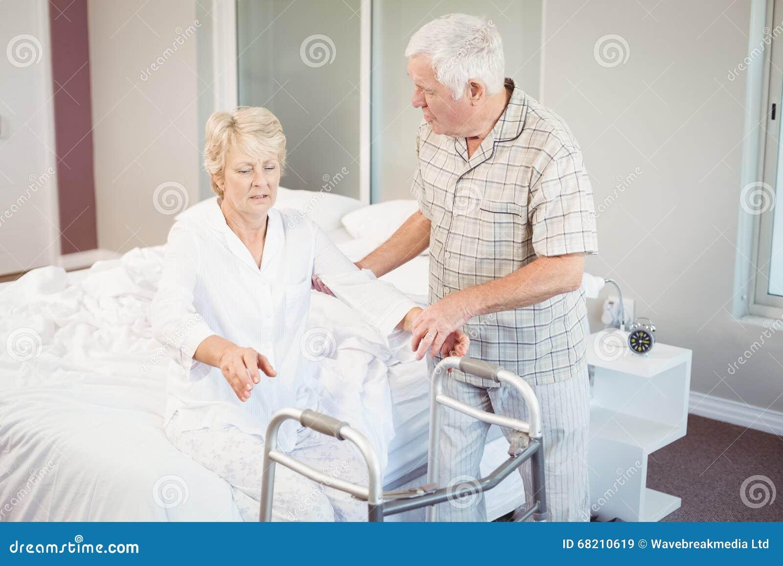 Älterer Mann, der kranke Frau beim Aufstehen vom Bett unterstützt