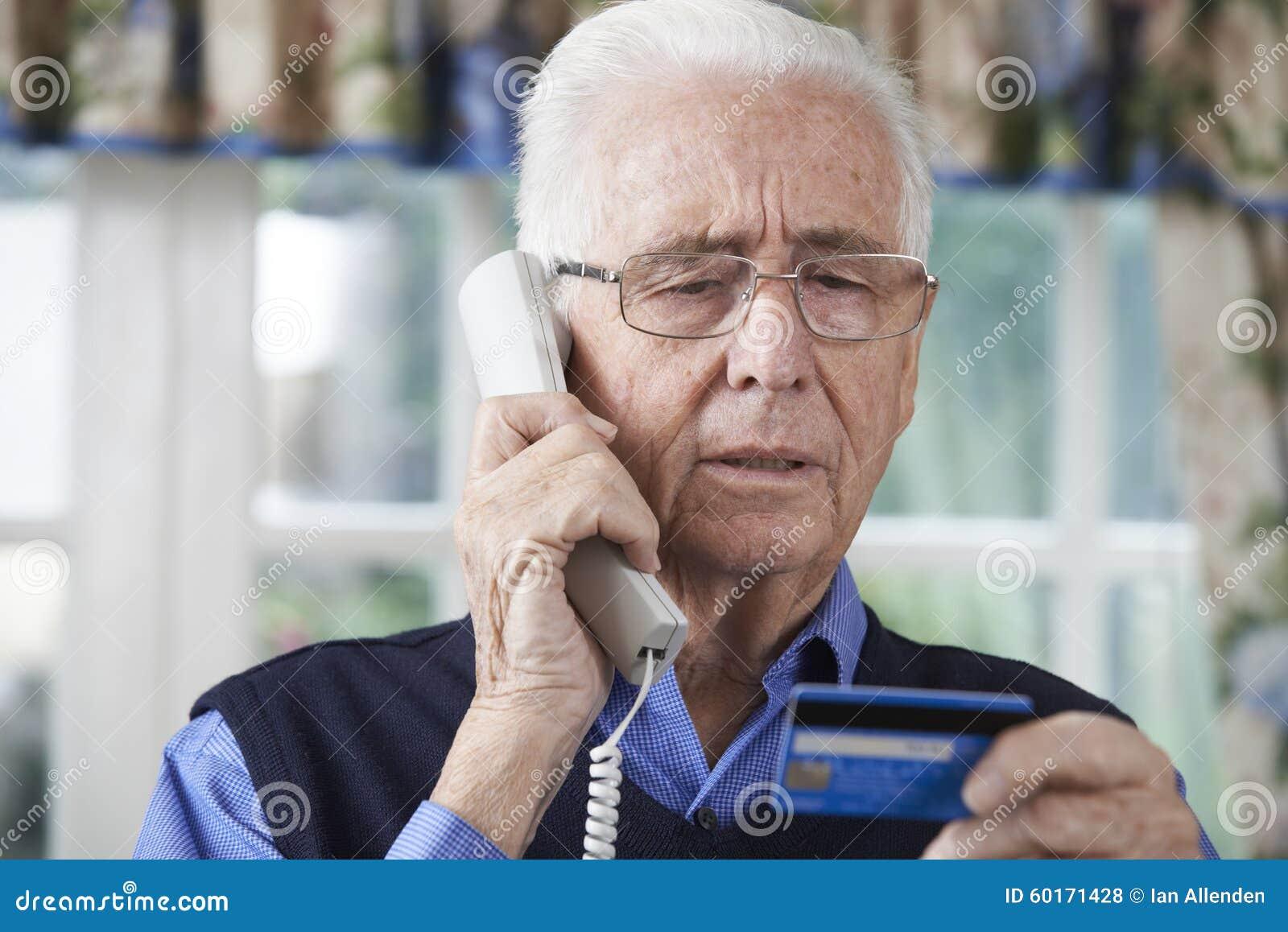 Älterer Mann, der Kreditkarteam Telefon spezifiziert