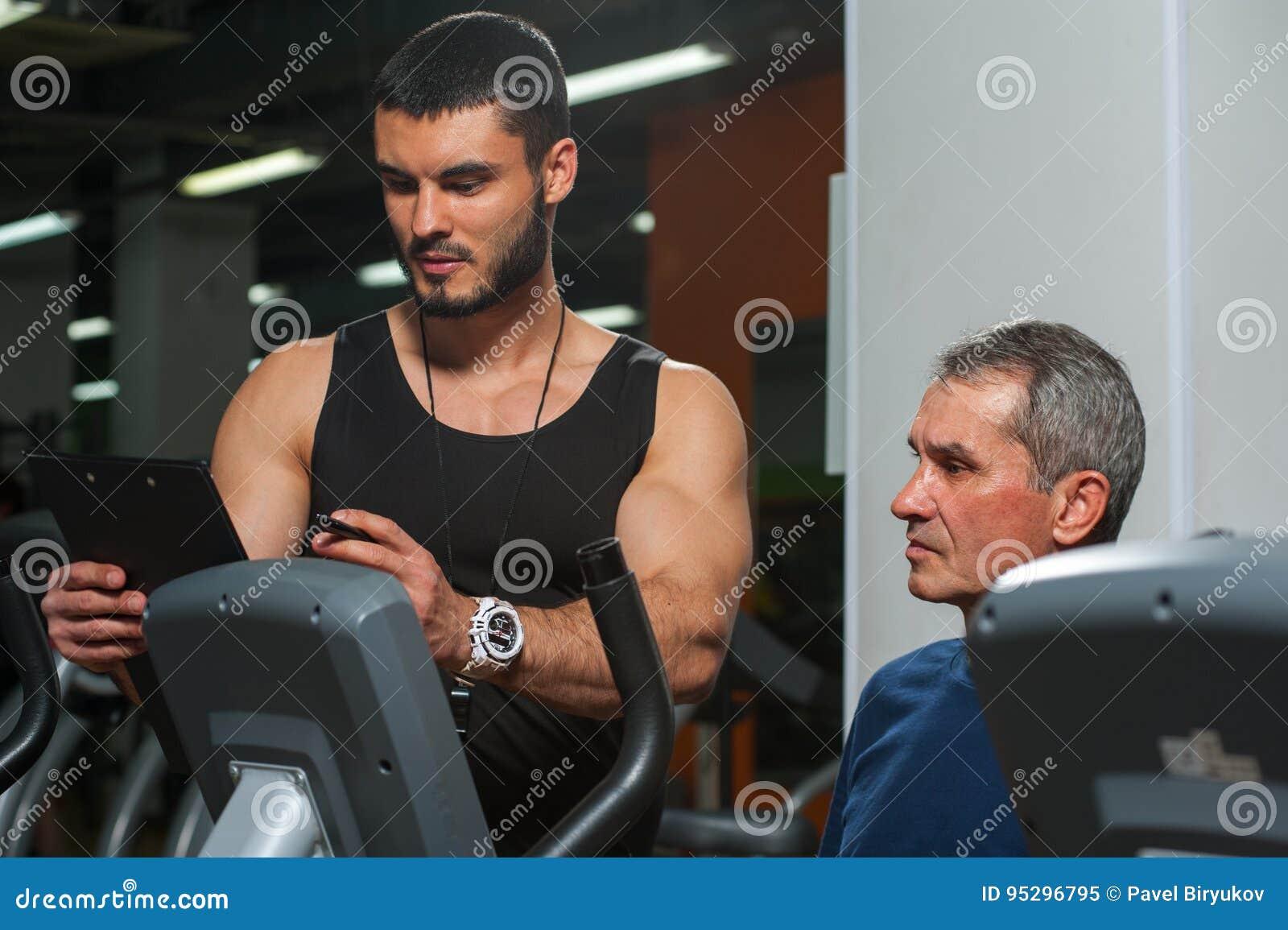 Älterer Mann, der mit persönlichem Trainer in der Turnhalle arbeitet