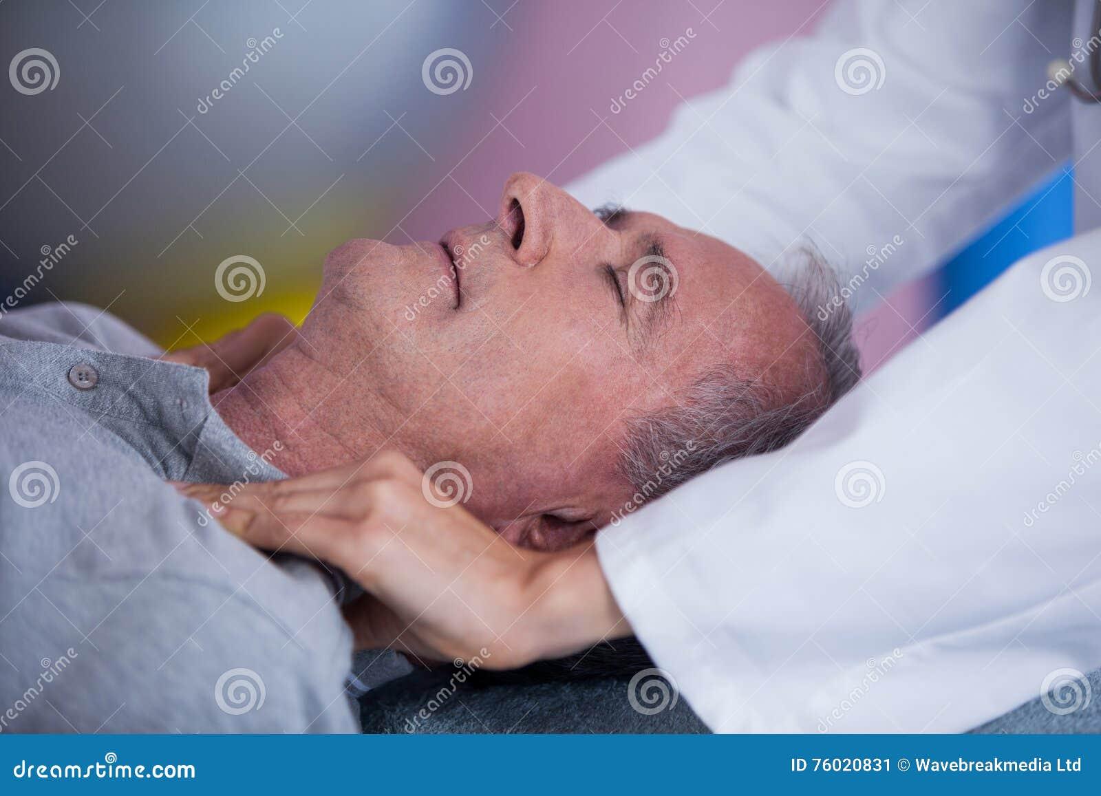 Älterer Mann, der Schultermassage vom Physiotherapeuten empfängt