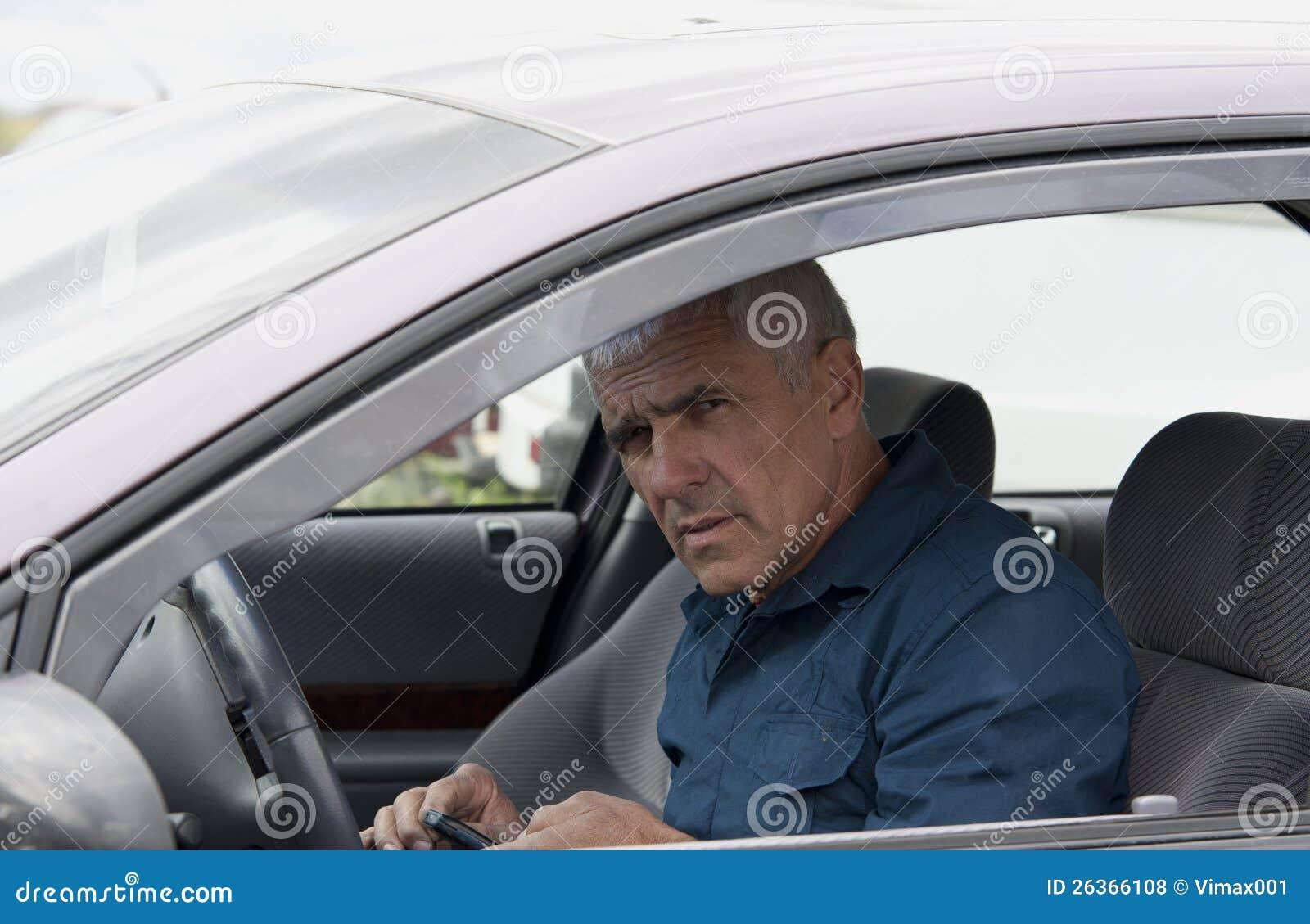 Älterer Mann im Auto mit Telefon