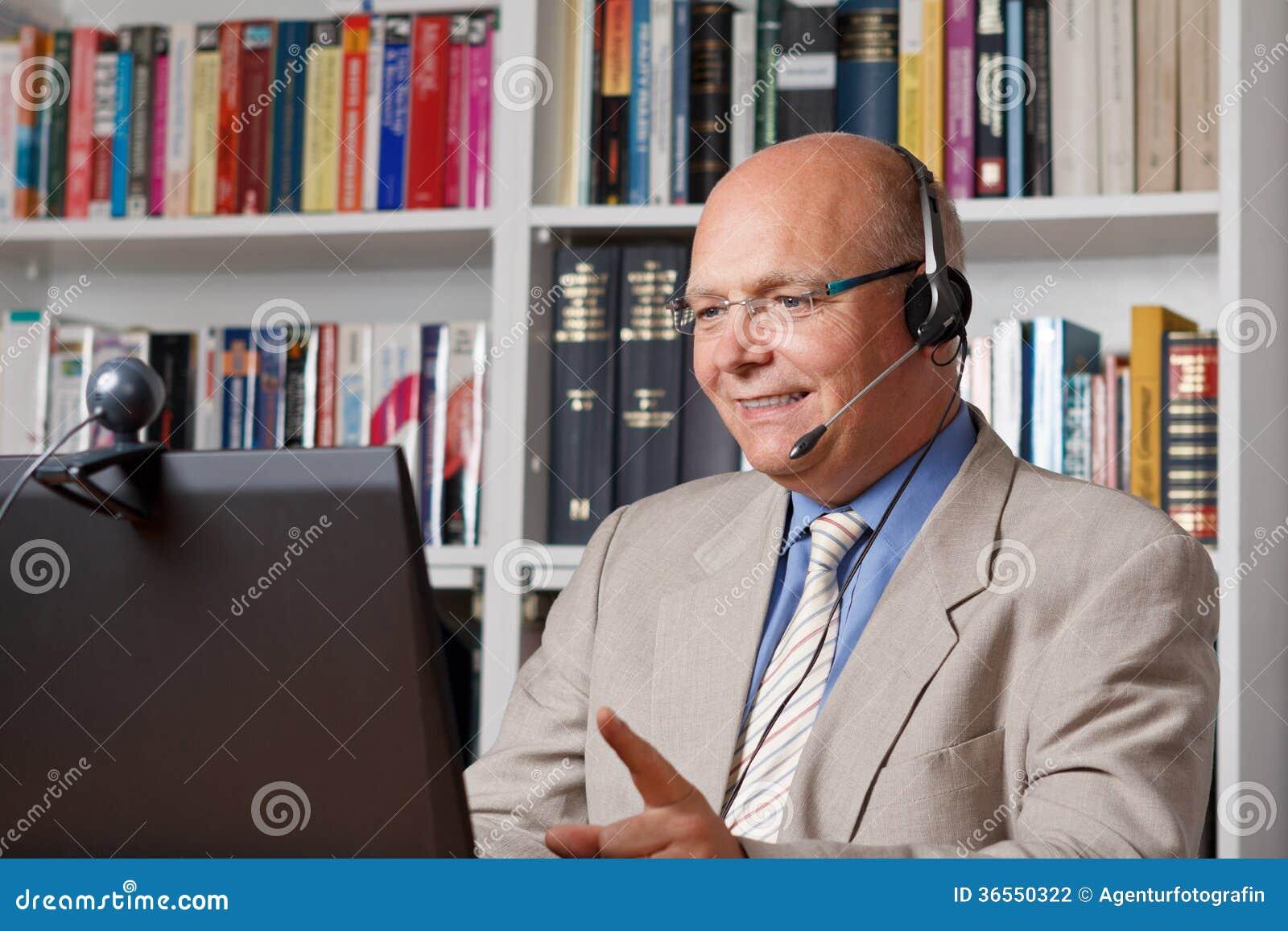 Älterer Mann mit Kopfhörern und Computer