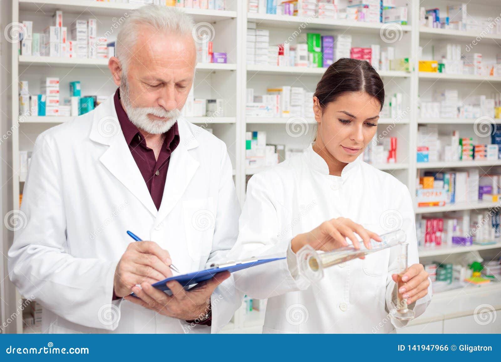Älterer Mann und junge weibliche Apotheker, die Chemikalien in einem Drugstore mischen