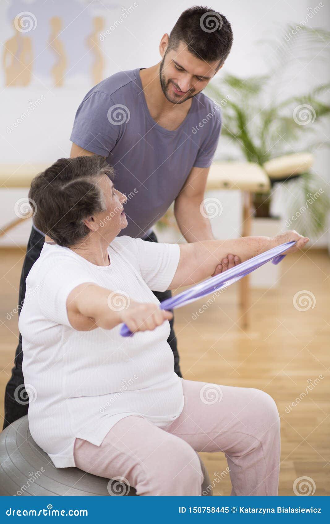 Älterer Pensionär, der mit Widerstandbändern mit ihrem Berufsphysiotherapeuten trainiert