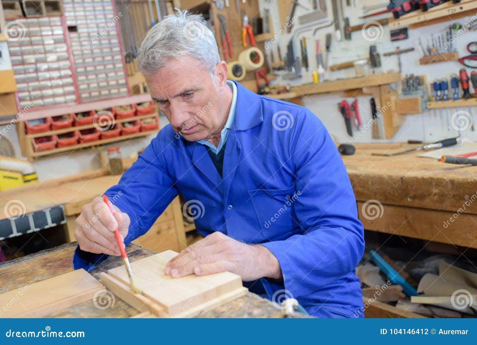 Älterer Tischler, der Bürste auf Stückholz in der Werkstatt verwendet