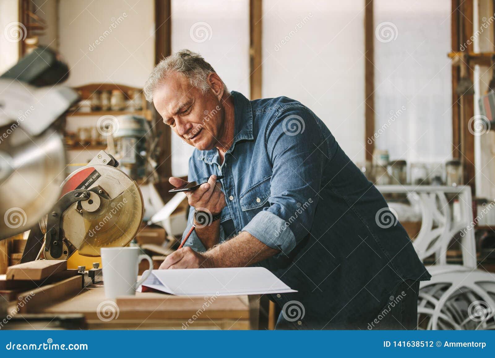 Älterer Tischler, der an seiner Werkstatt arbeitet