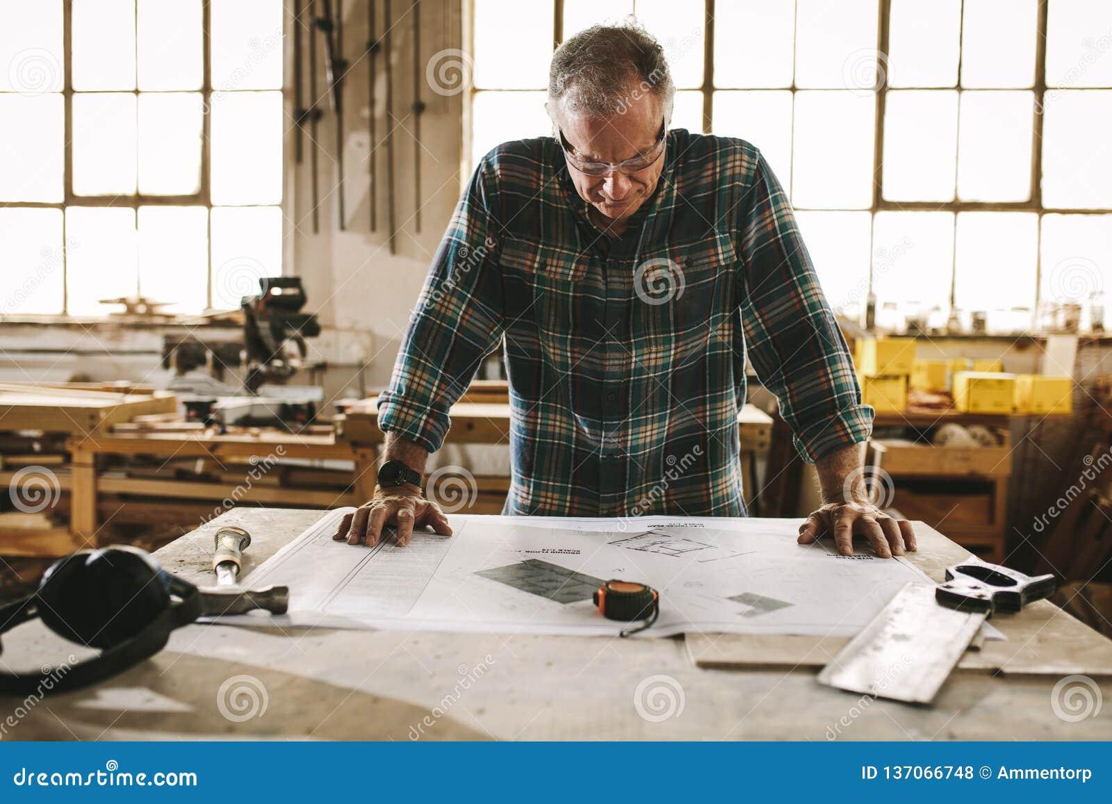 Älterer Tischler, der Zeichnung in der Werkstatt überprüft
