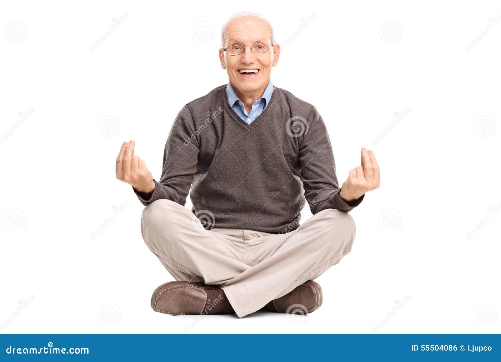 Älteres Herrmeditieren gesetzt auf dem Boden